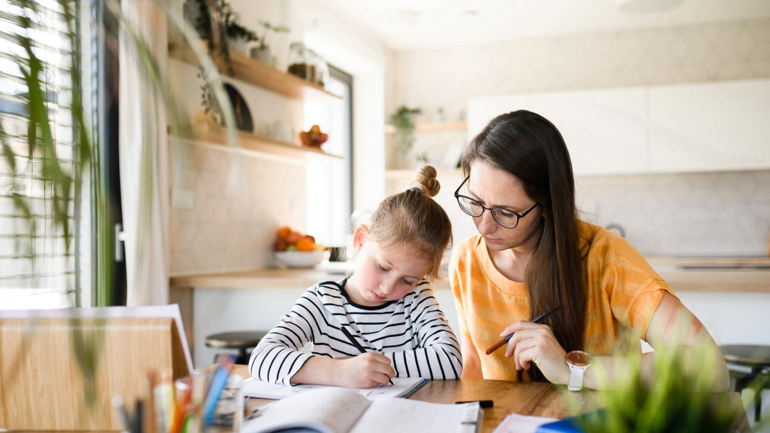 mother helping daughter with remote learning, using principles of social and emotional learning