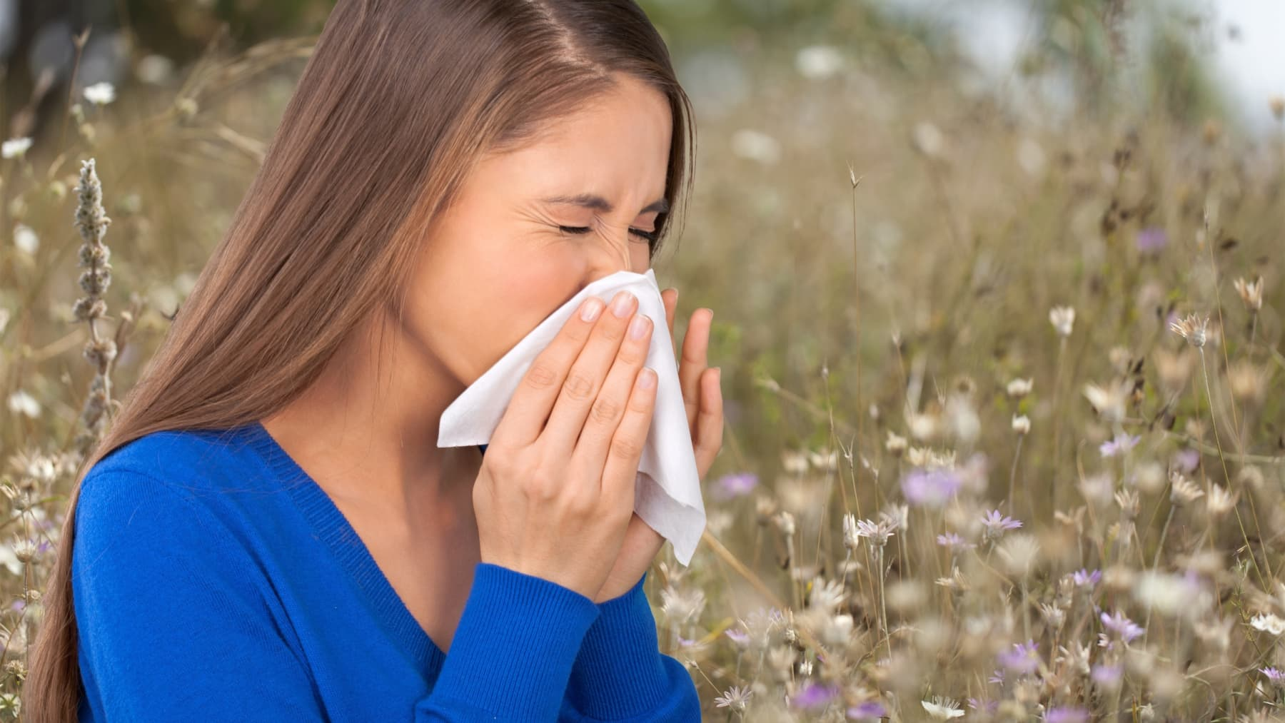 A woman in a blue shirt who has seasonal allergies sneezes into a tissue outside.