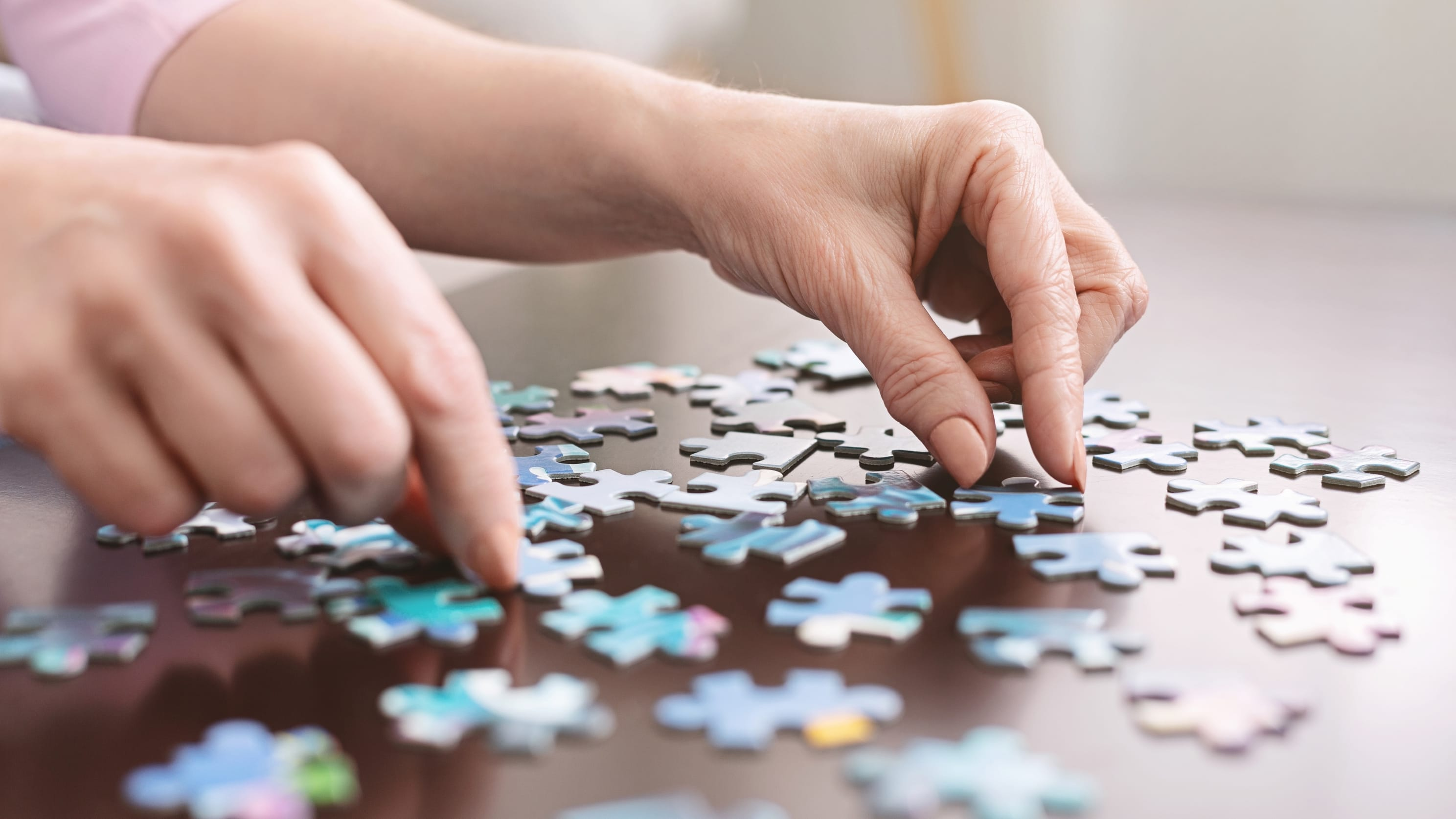 elderly person putting together a jigsaw puzzle, representing the confusion of dementia