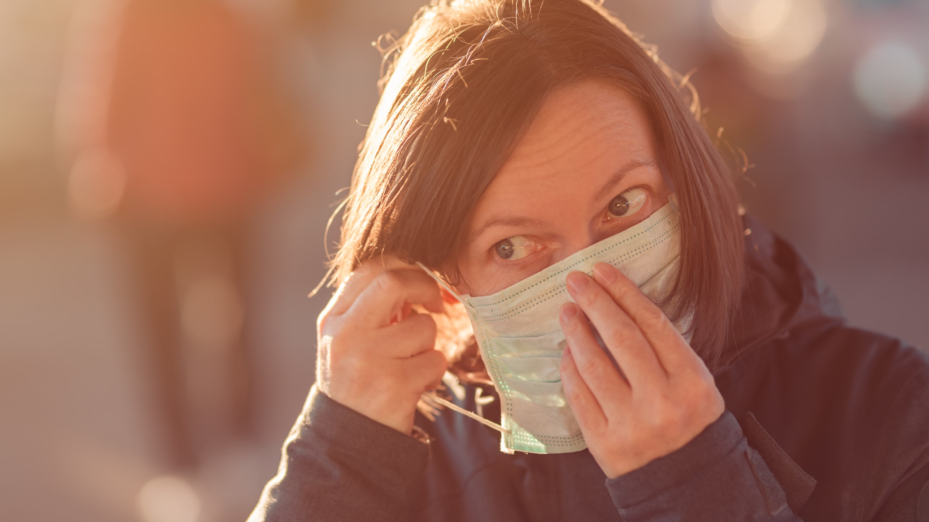 Woman with face protective mask standing on the street, possibly with post-COVID-19 symptoms
