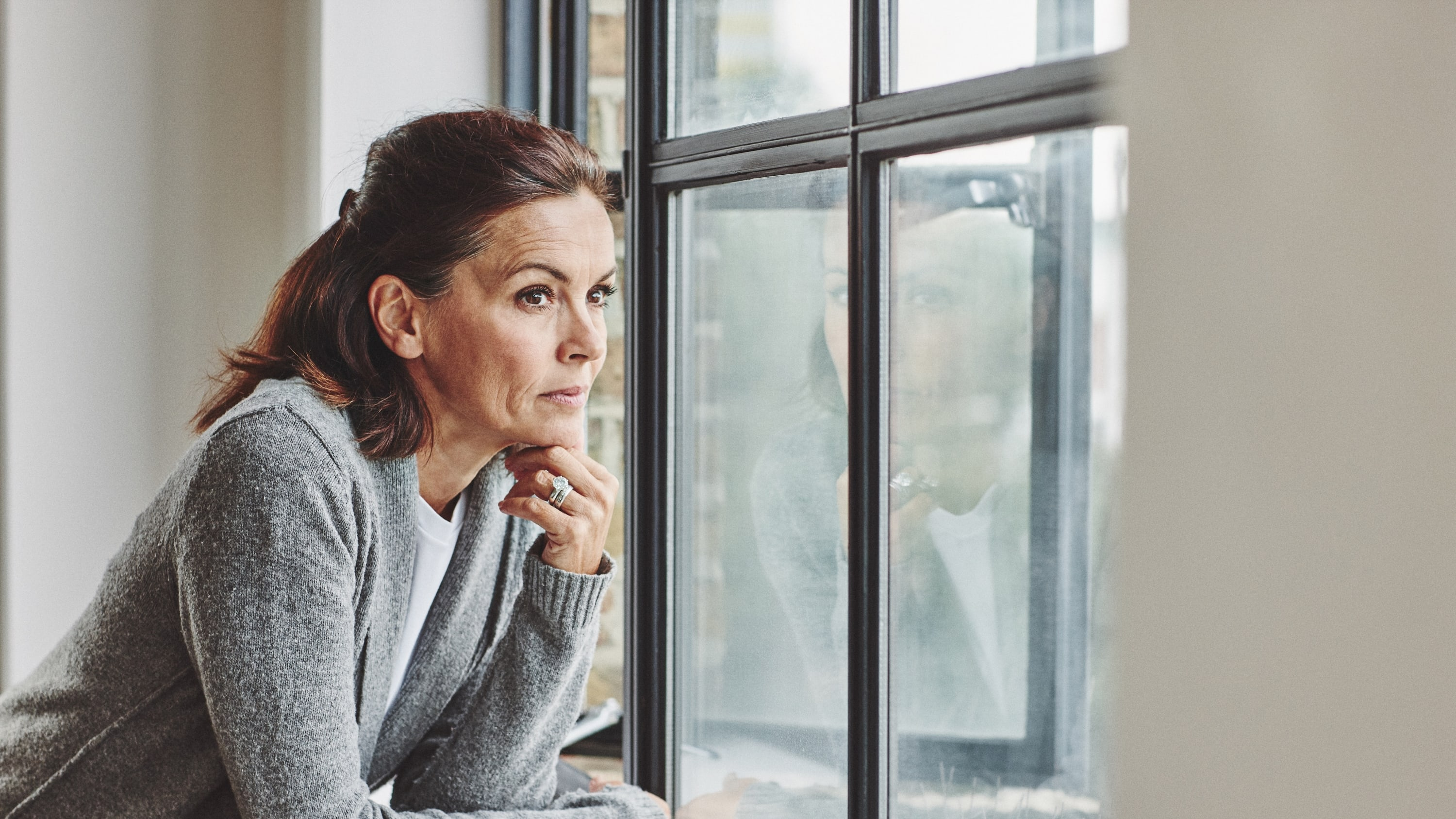 Thoughtful mature woman standing by the window, thinking about transvaginal mesh for pelvic organ prolapse