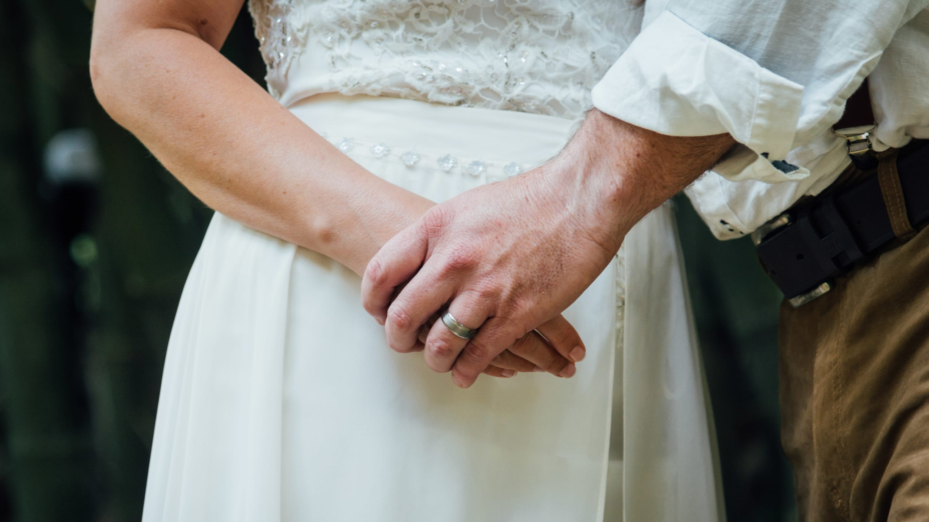 A newly married couple hold hands, closeup is on the hands.