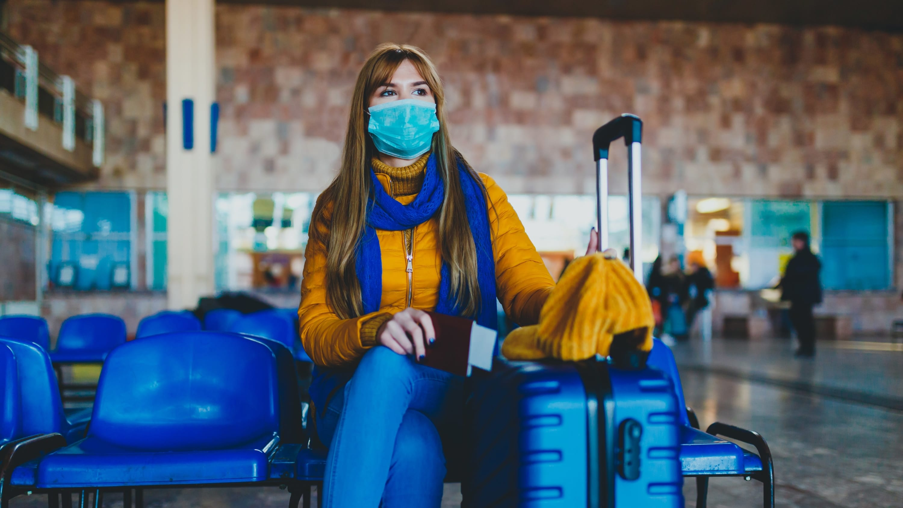 woman in mask at airport, following CDC guidelines for COVID-19 infection prevention
