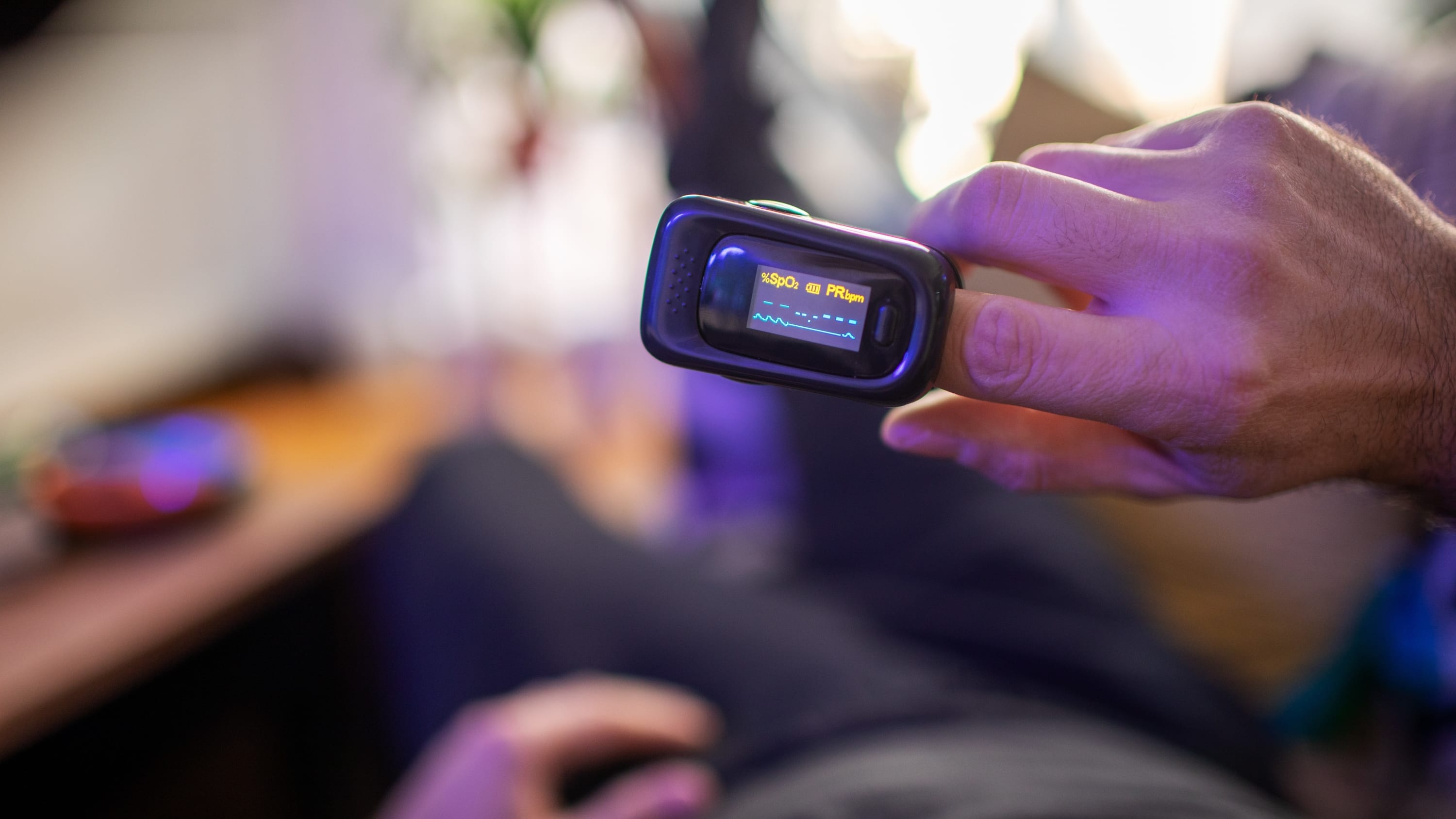 person with at-home pulse oximeter, possibly used to monitoring a COVID-19 symptom