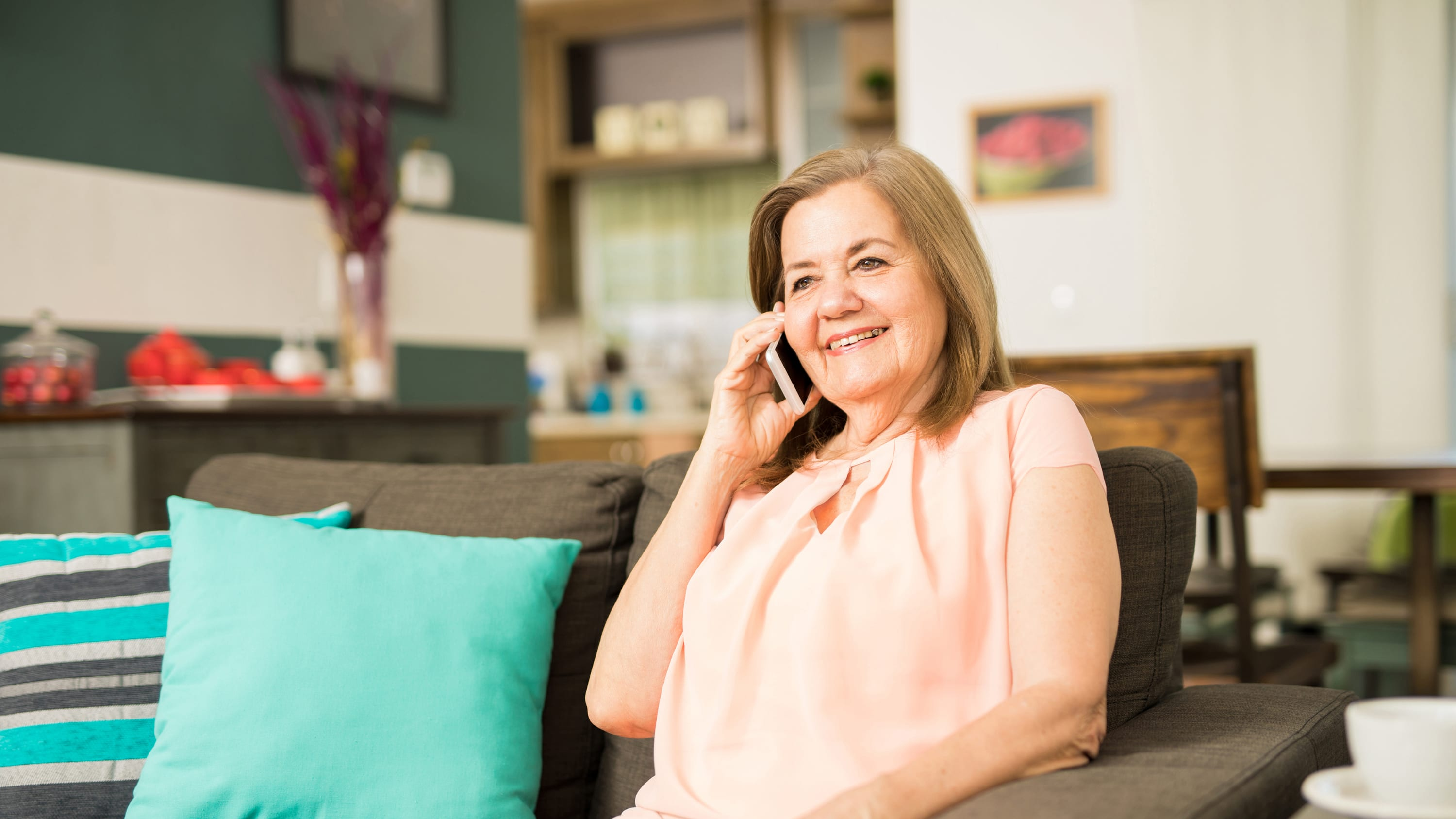A middle-aged woman who may have heart arrhythmia sits on a couch talking on a cell phone.