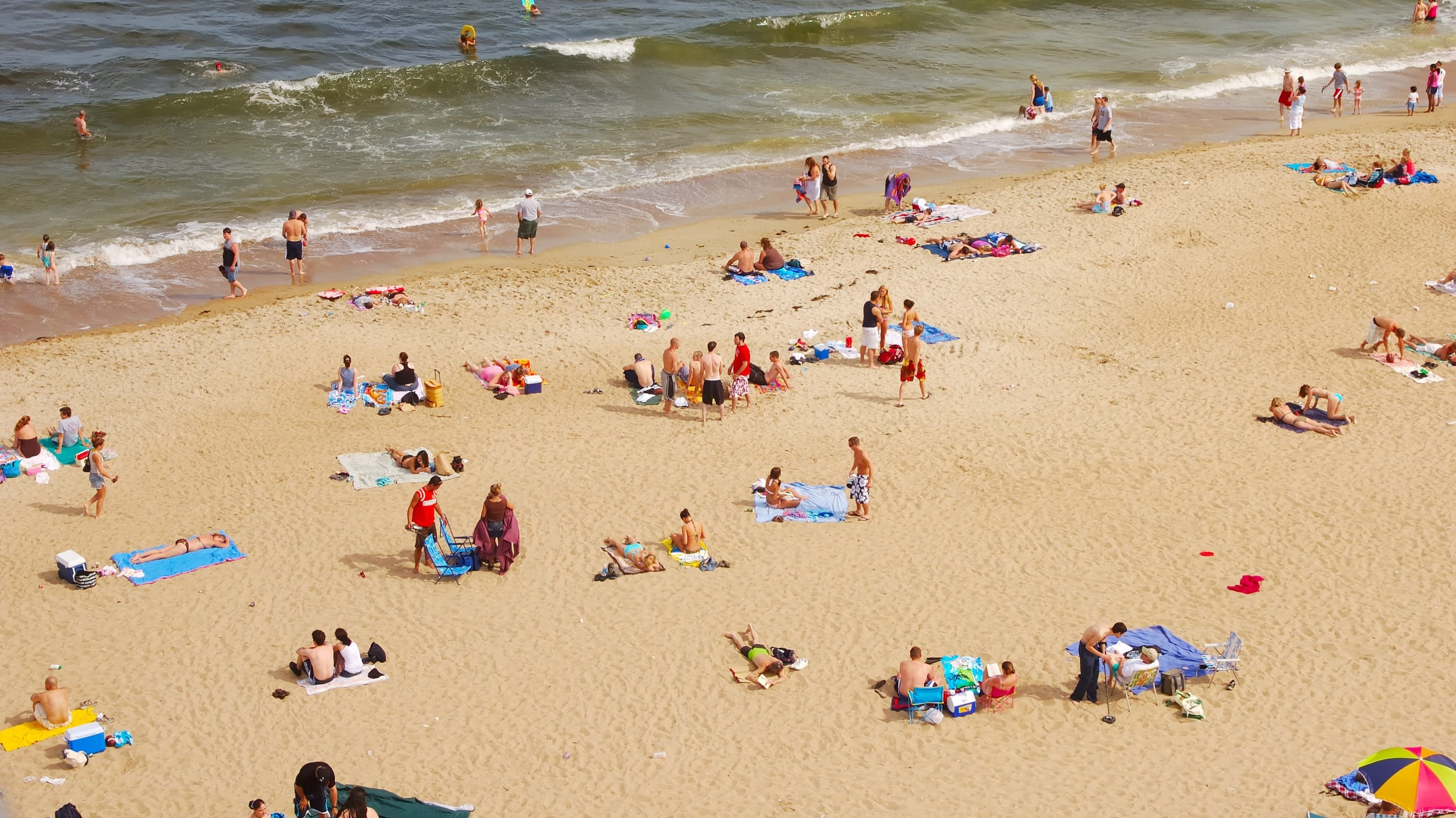 people at a crowded beach, as the country reopens amid COVID-19