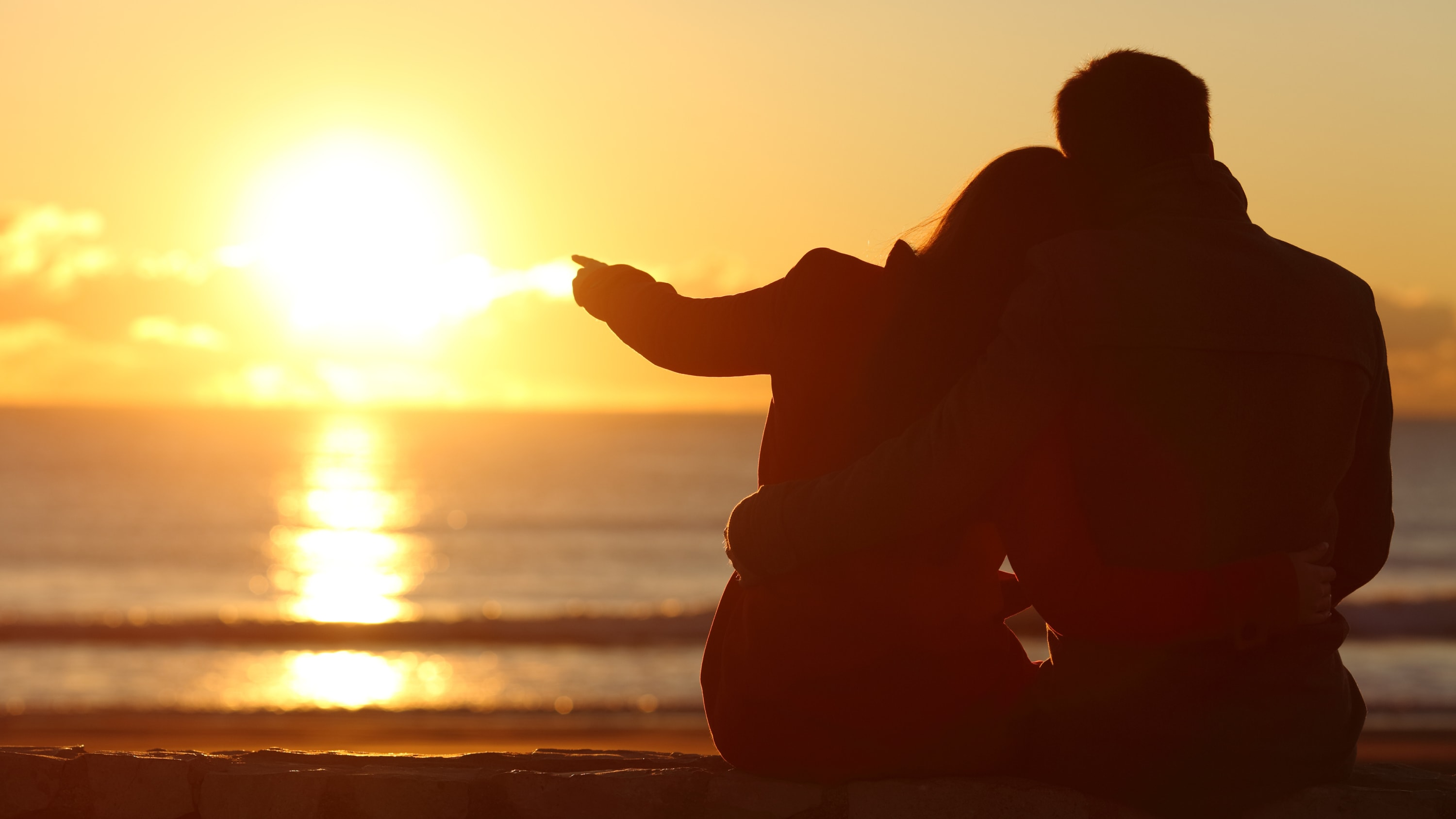 A man and woman sit on a beach and admire the sunset.
