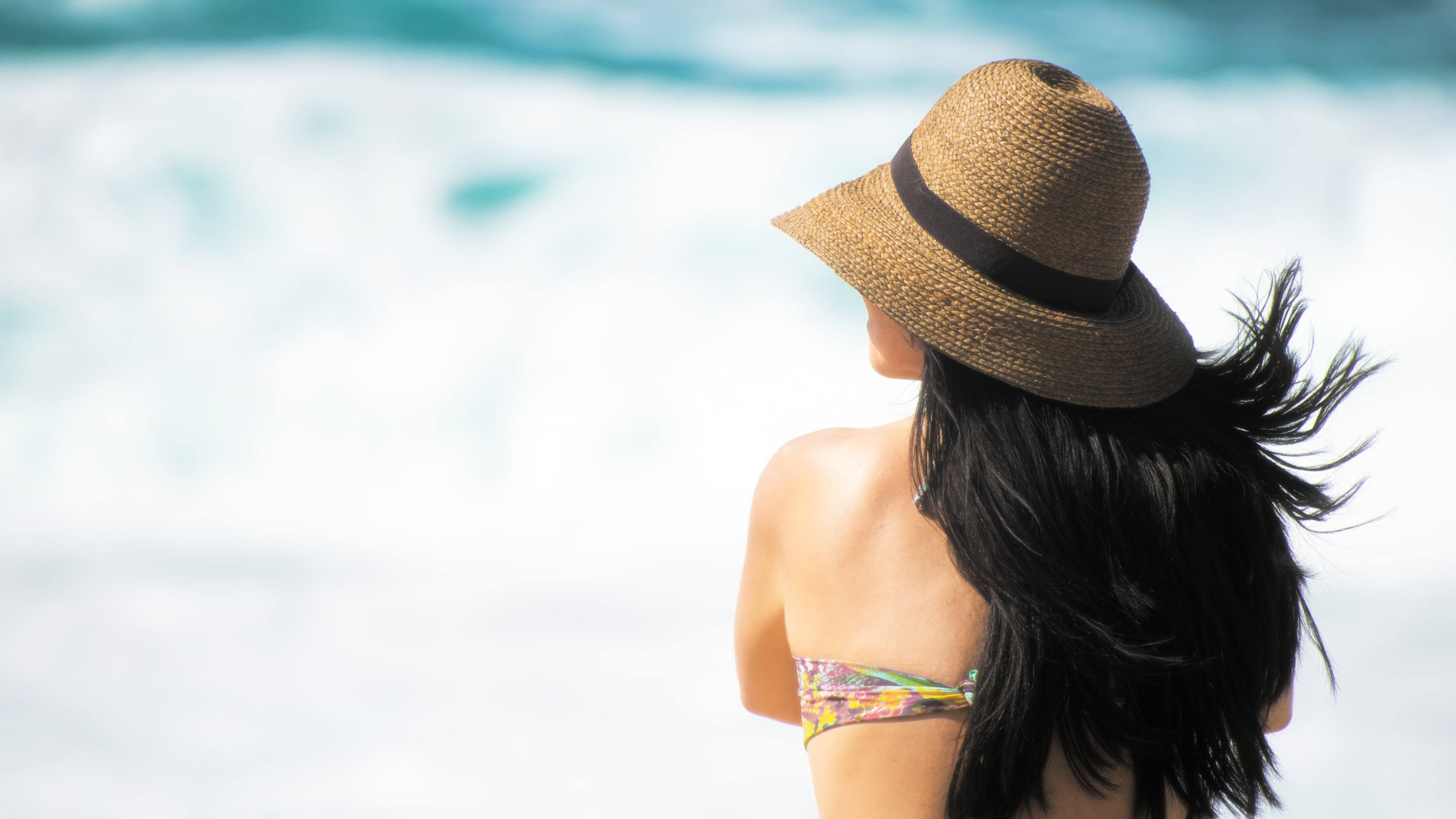 Woman on beach with long dark hair wearing hat.