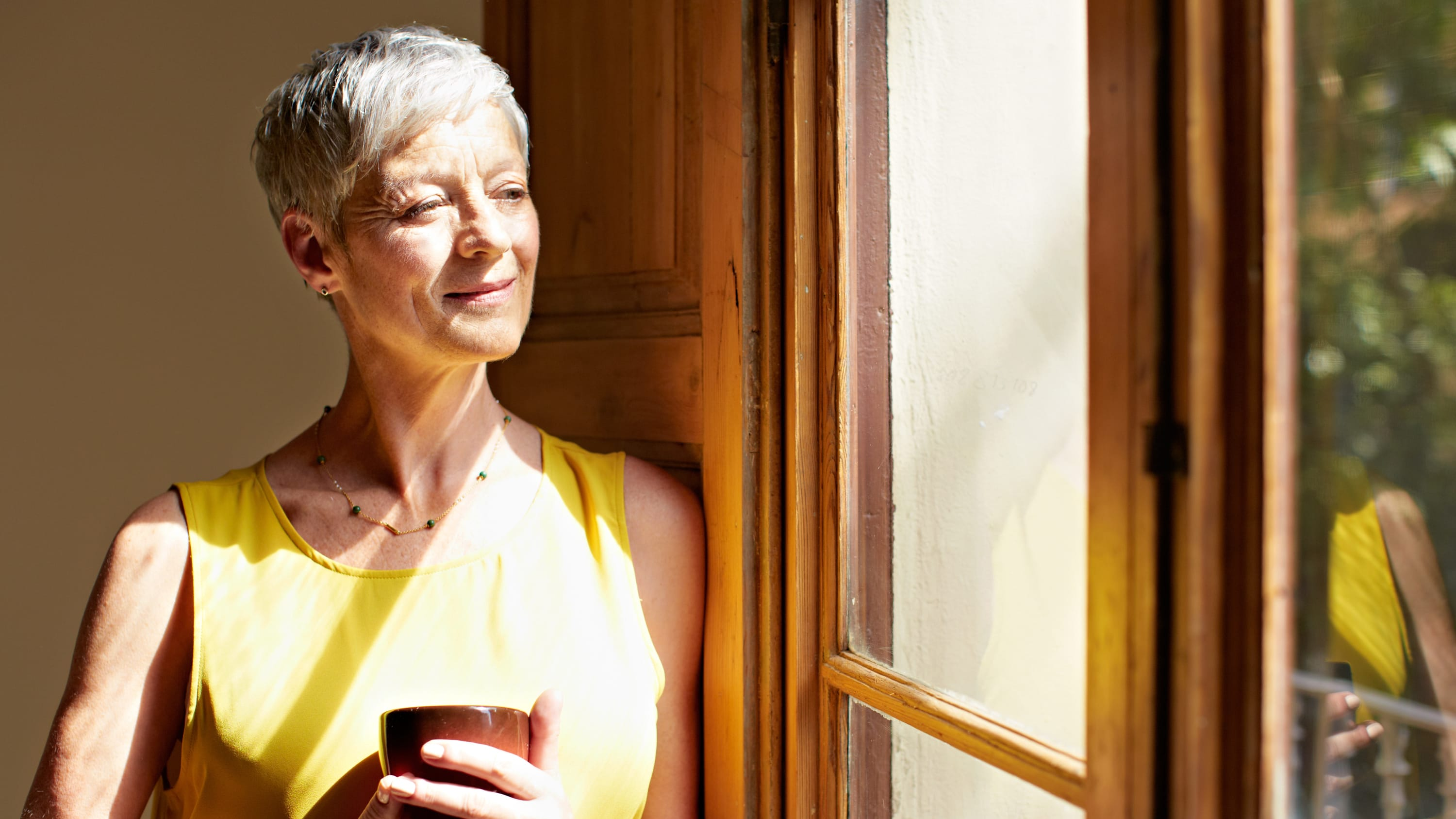 A woman looking out a window, possibly thinking about radiation therapy as a treatment for breast cancer.