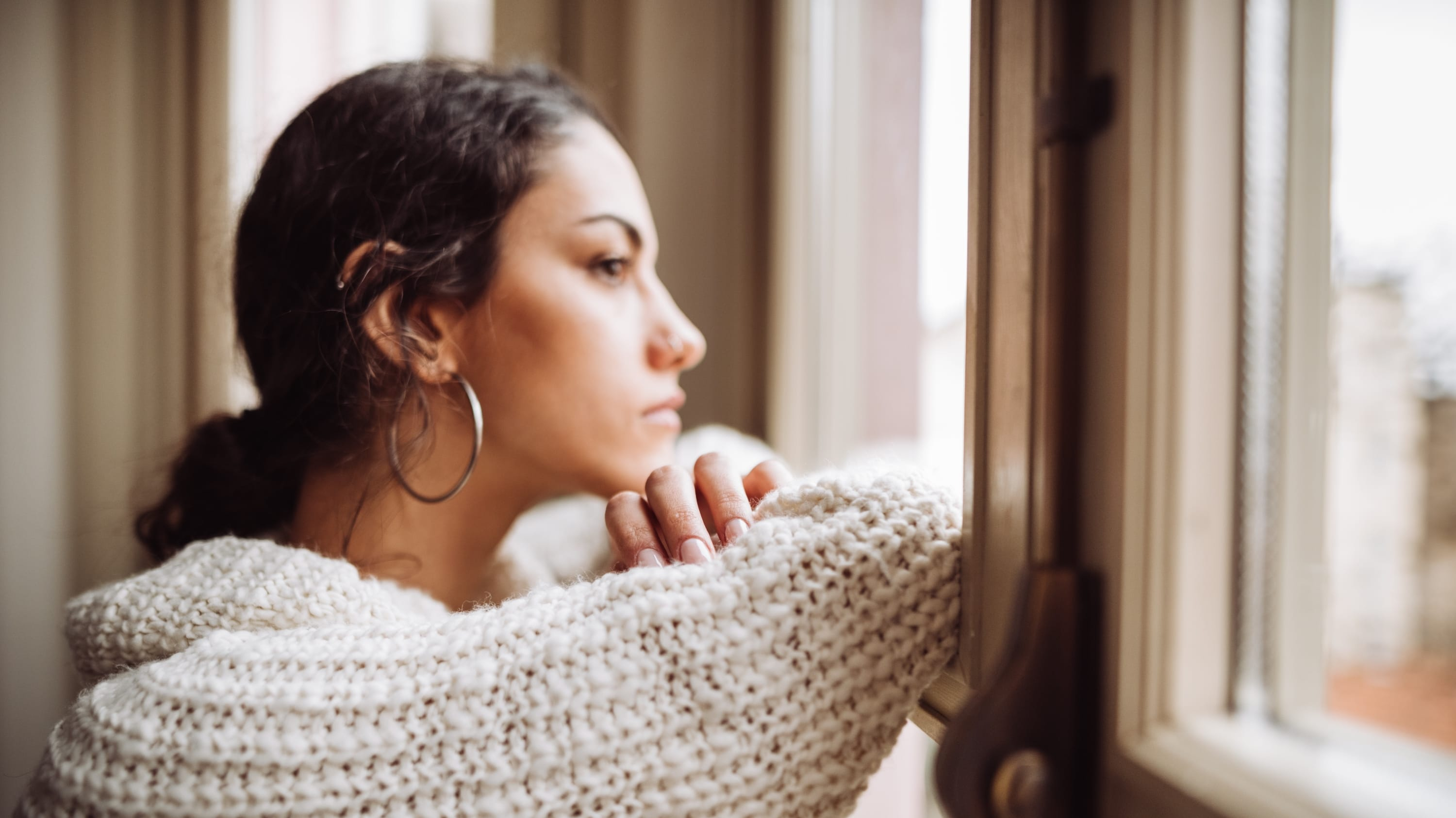 pensive woman in front of the window, thinking about advanced directives, especially amid COVID