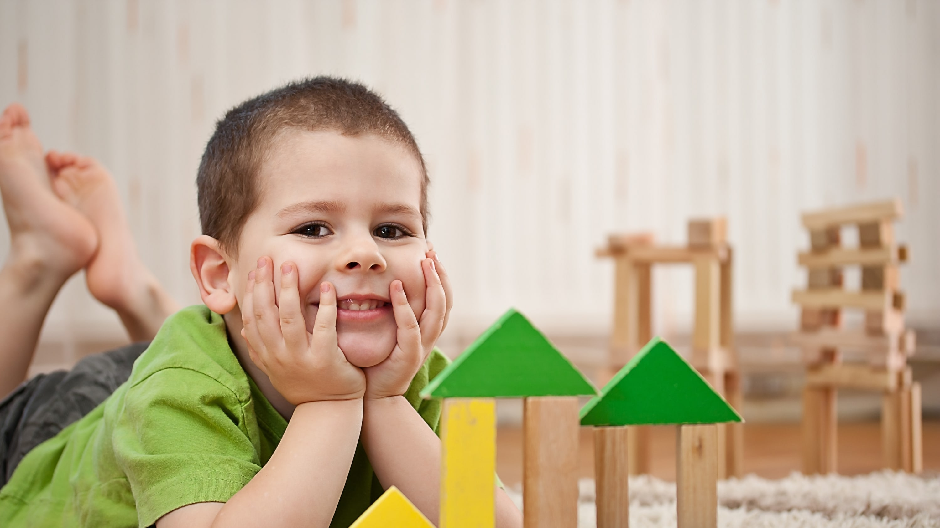 a young child sits in front of his wooden block tower, possibly waiting for an appointment to discuss developmental delay