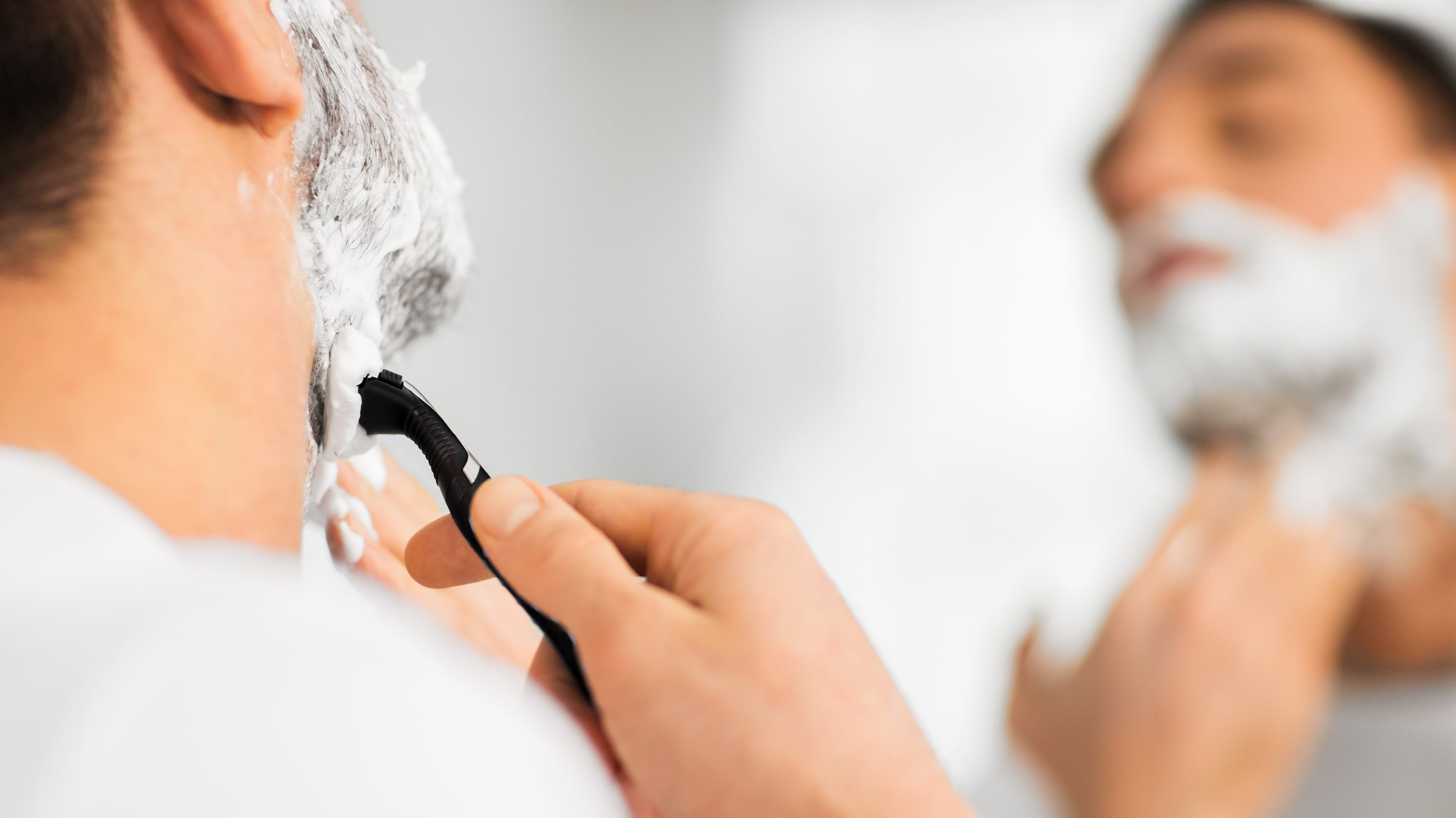A man is shaving in a mirror. He is wearing a white t-shirt.