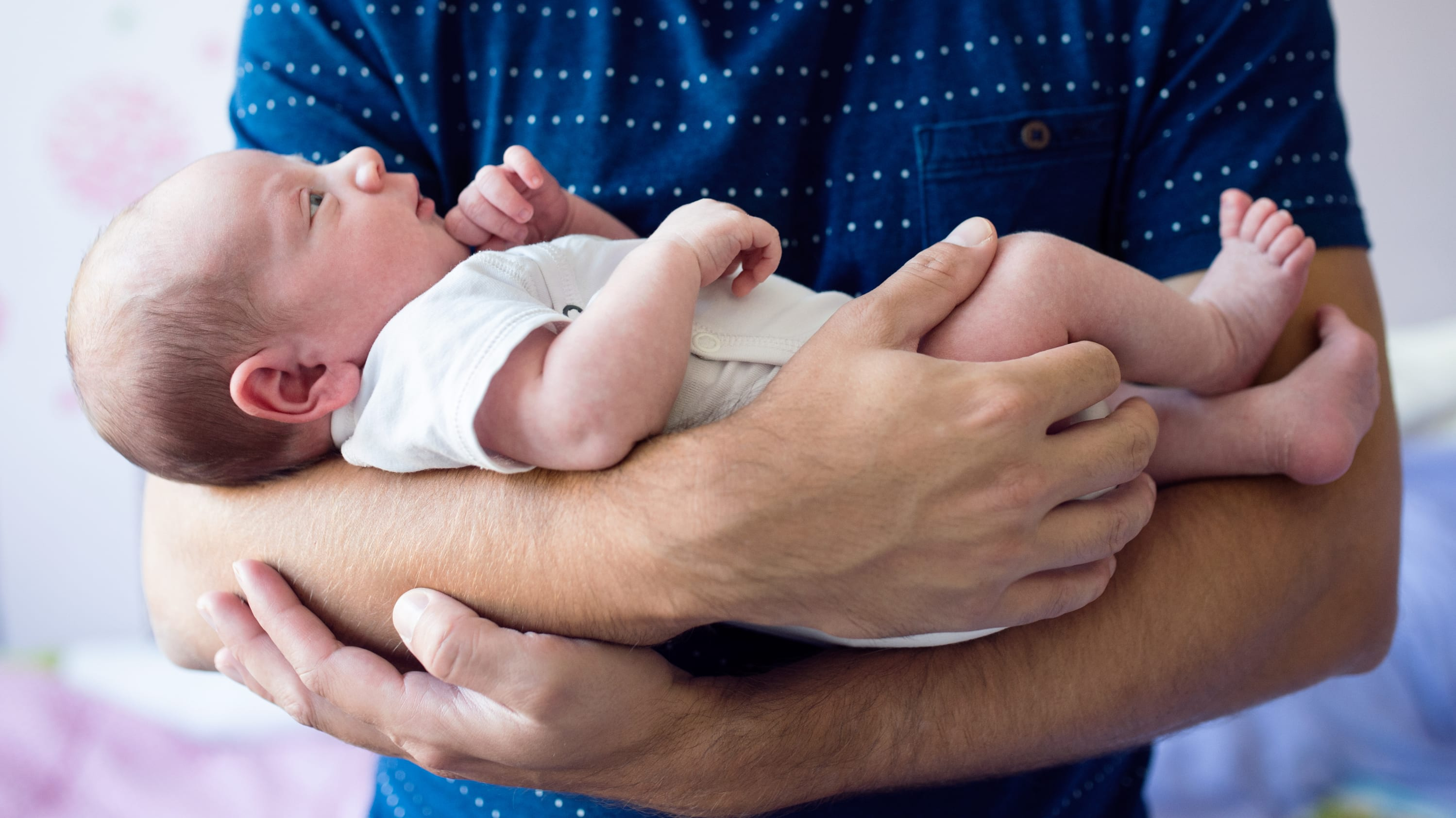 A father cradles a newborn son with a congenital heart defect.