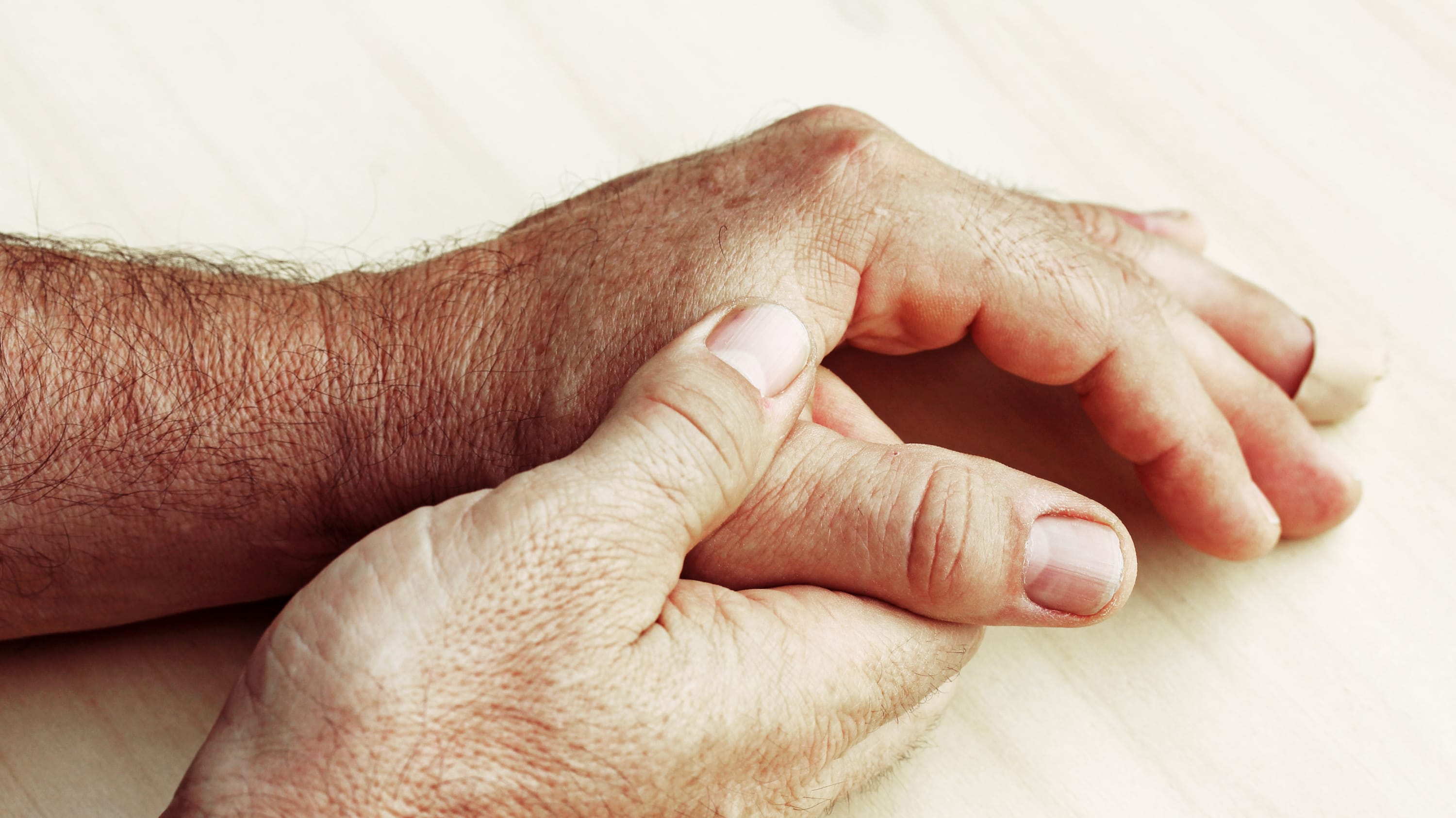 A person massages their hands, possibly because of Dupuytren's syndrome.