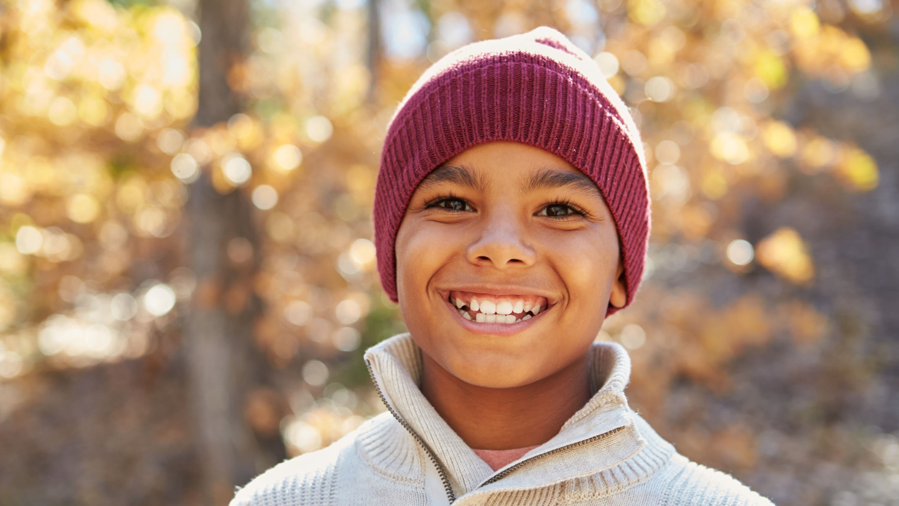 Boy who may have ADHD stands outside with a hat on, smiling.