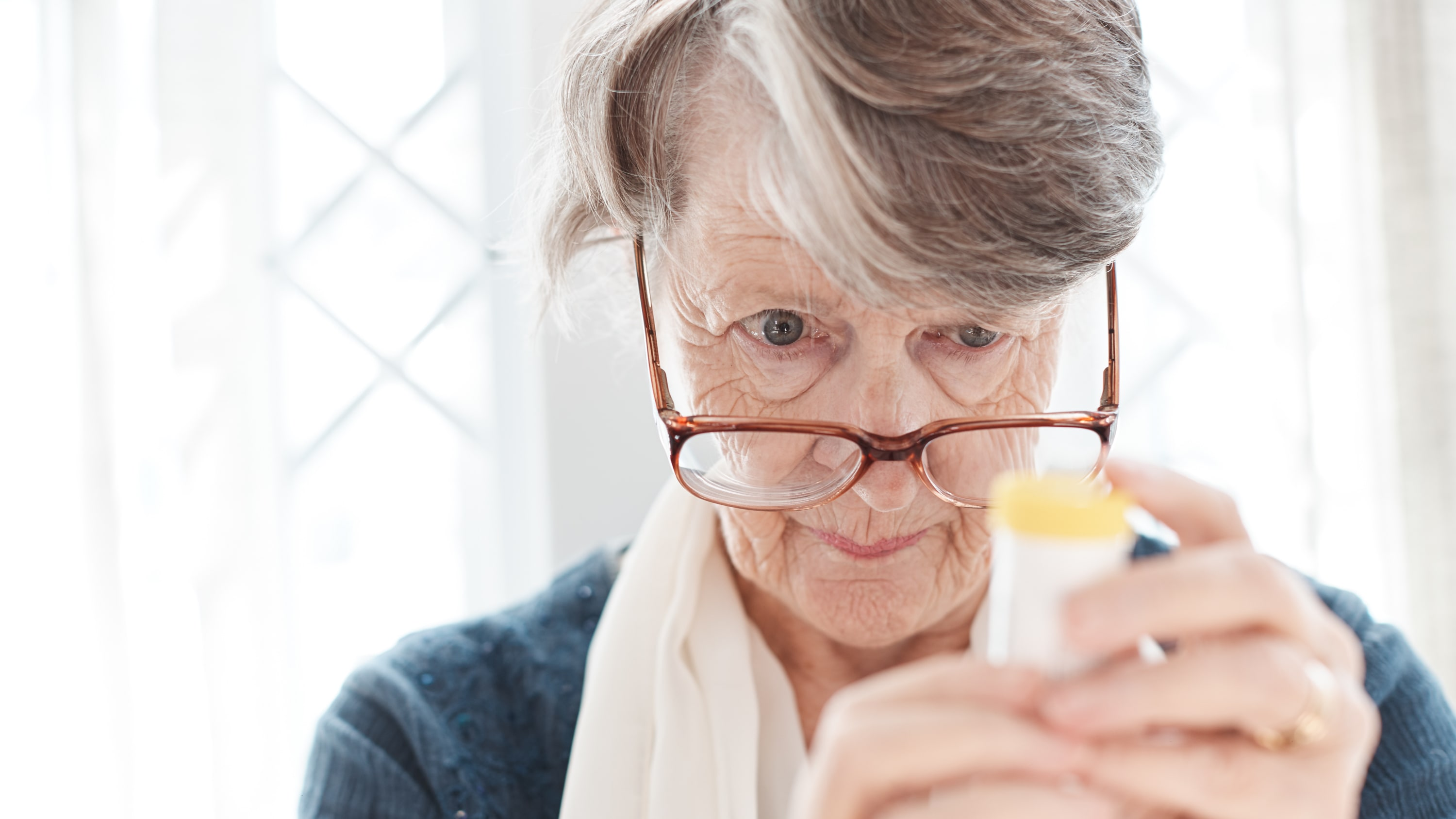 older woman trying to read prescription medication bottle