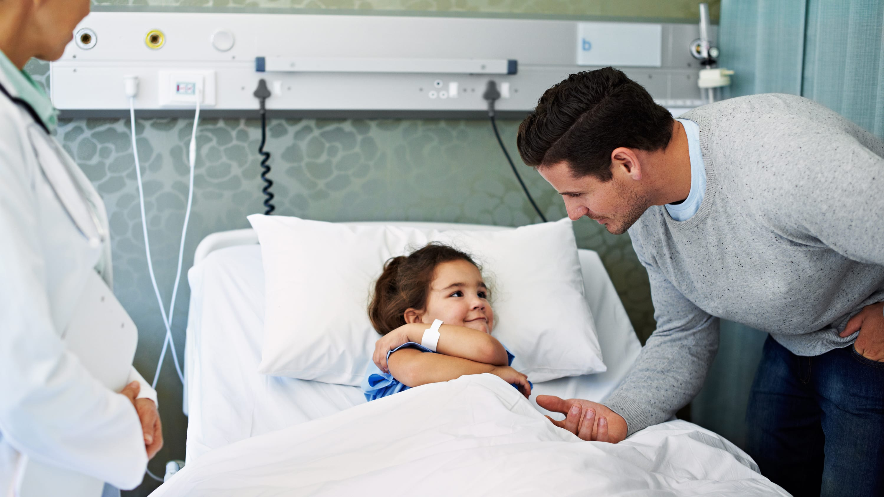 A child who had surgery for a congenital heart defect recovers in a hospital room.