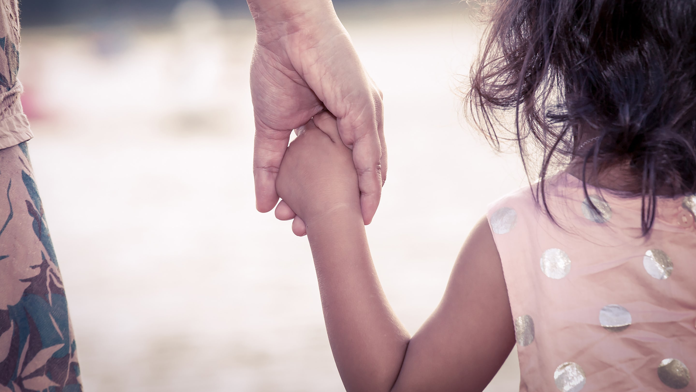 Little girl in a pink and white polka dot dress holds the hand of a parent who may be depressed.