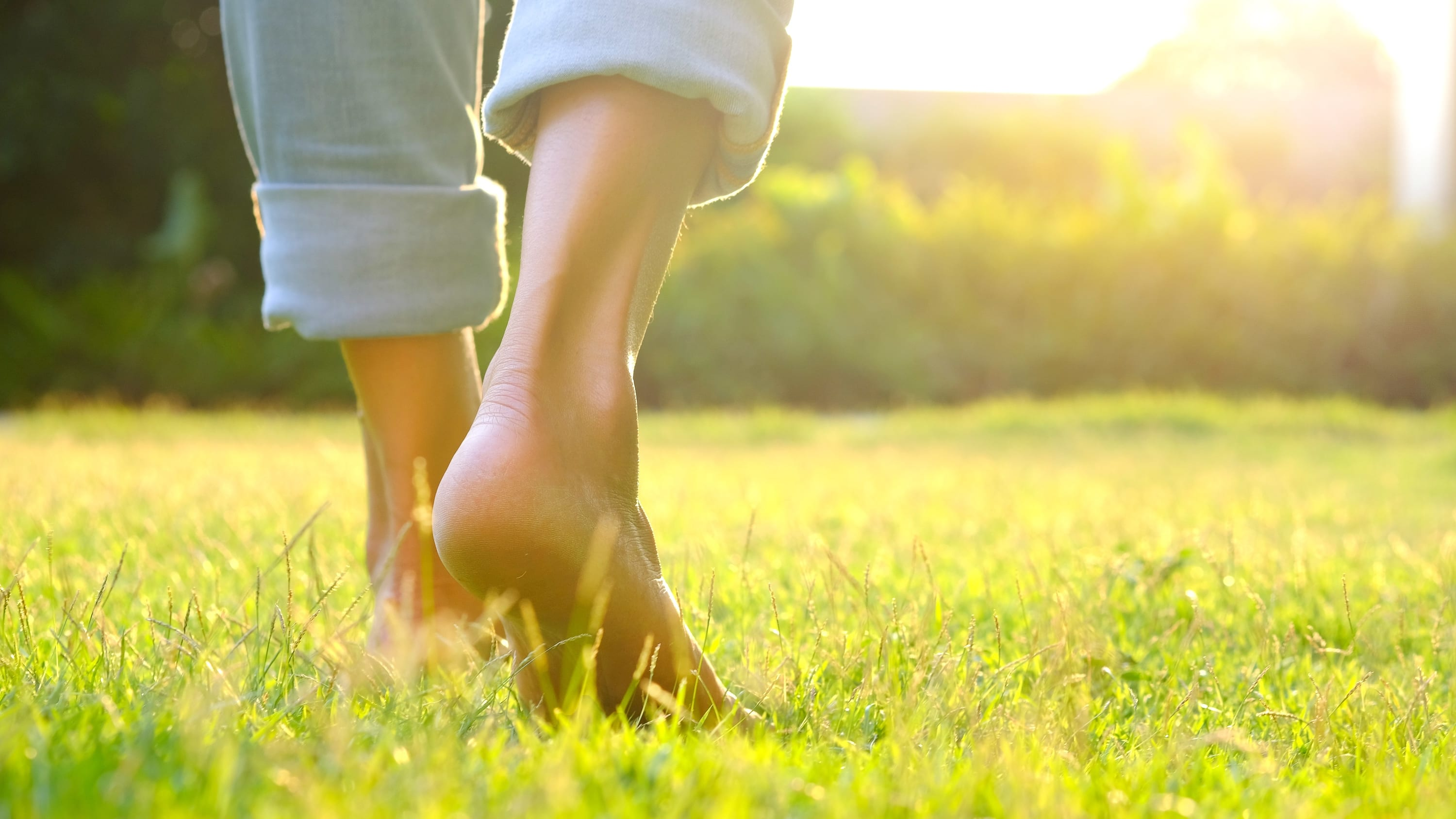 woman walking in grass after recovering from COVID-19