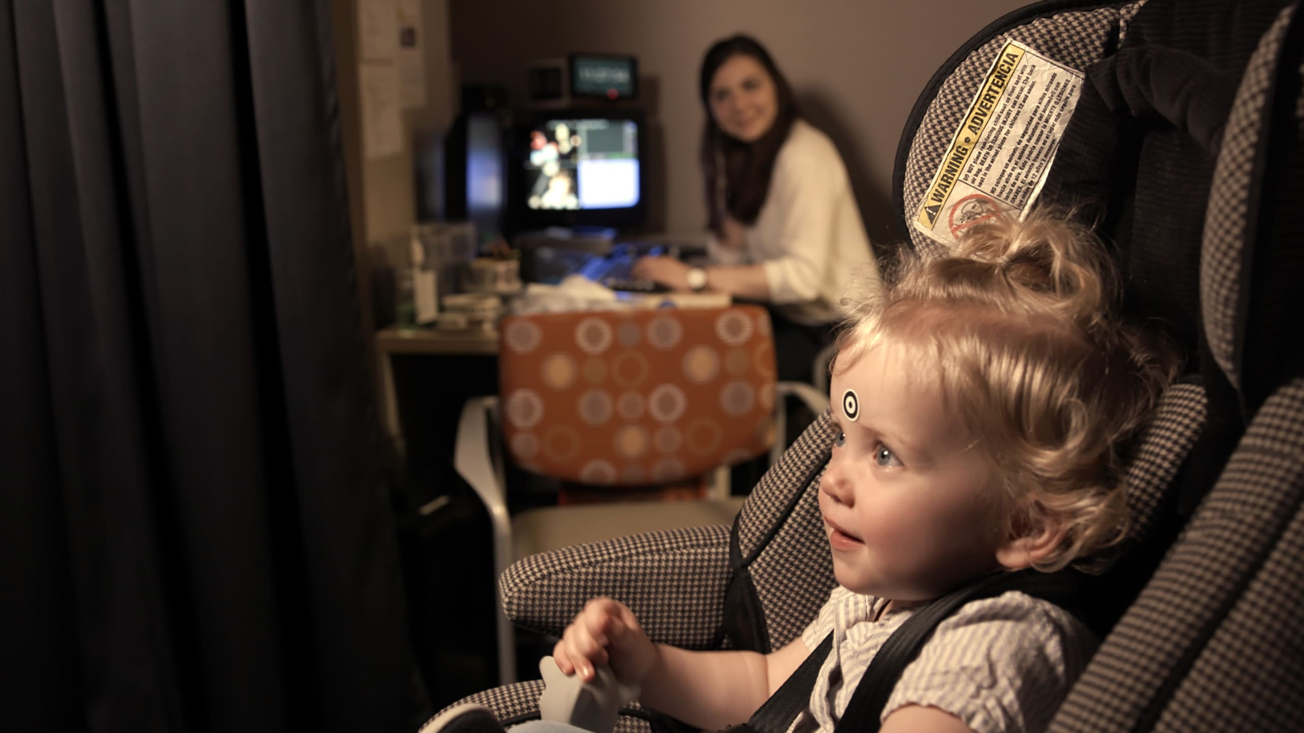A baby undergoes eye-tracking screening for early detection of autism.