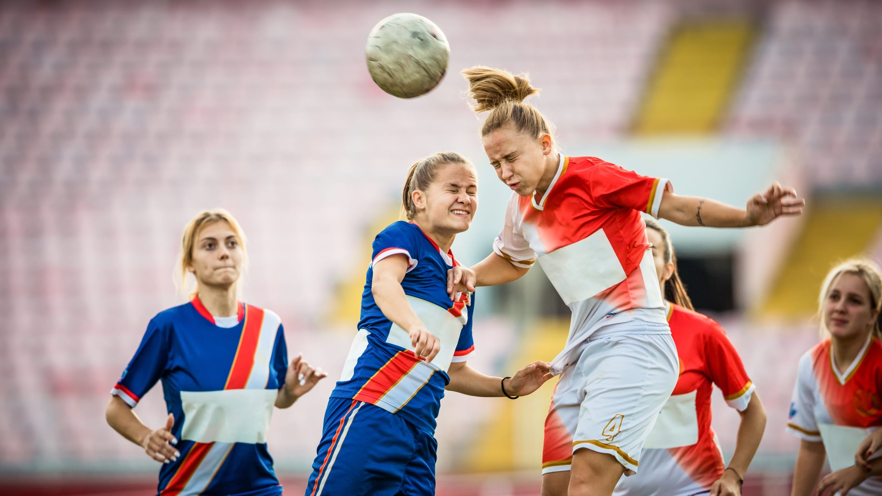 Two female soccer rivals heading the ball on a match, possibly at risk for concussion