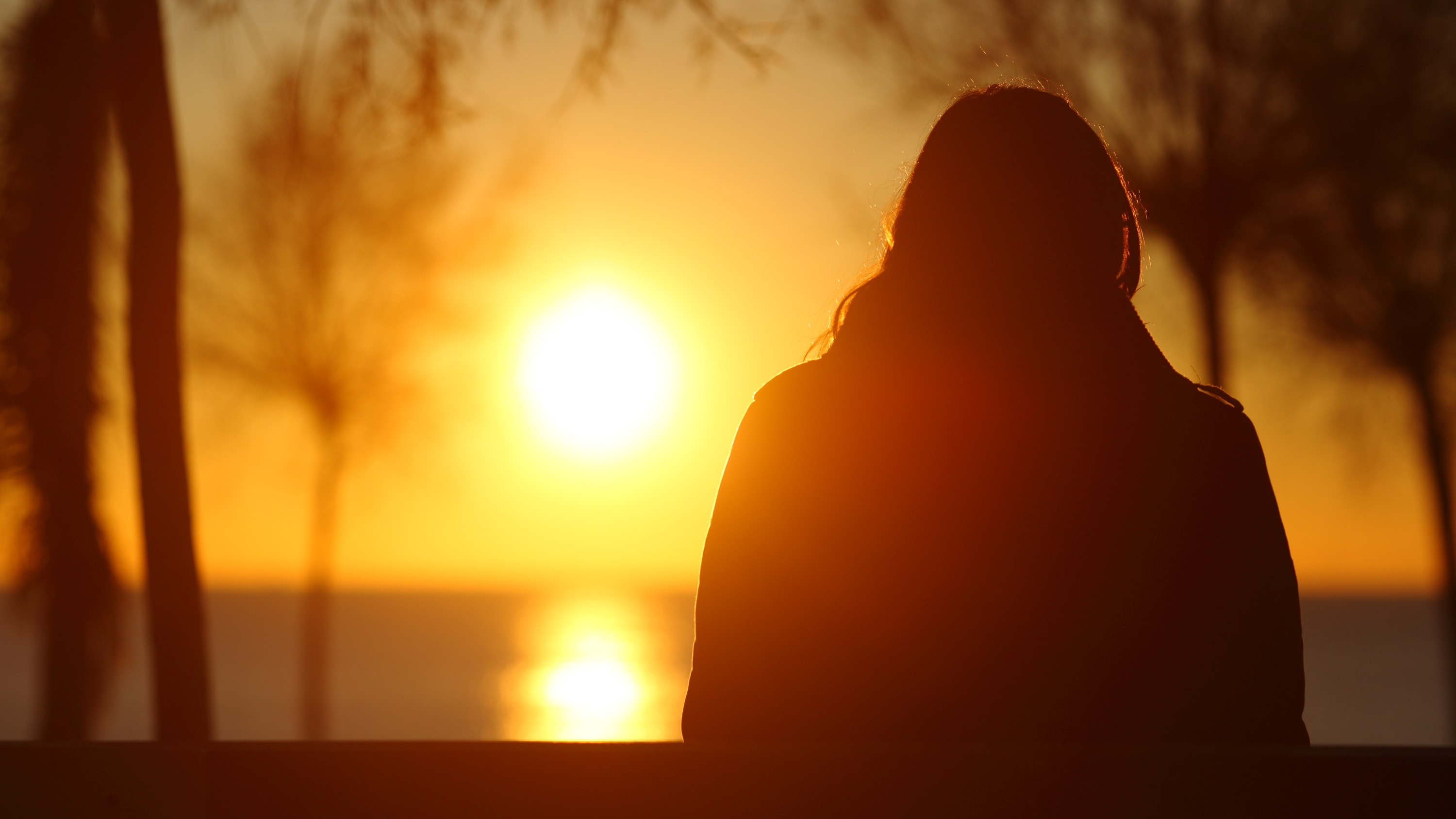 woman with seasonal affective disorder (SAD) looking at the sun, as possible light therapy