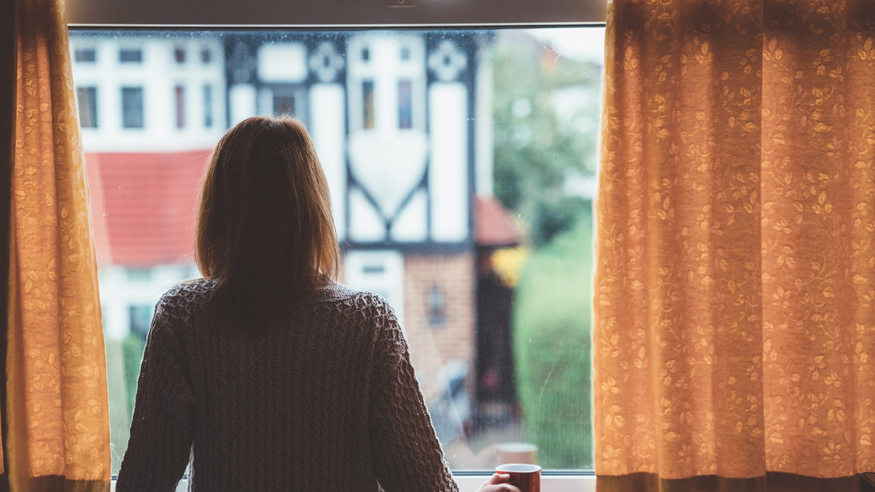 woman looking out a window, dealing with social isolation from COVID-19