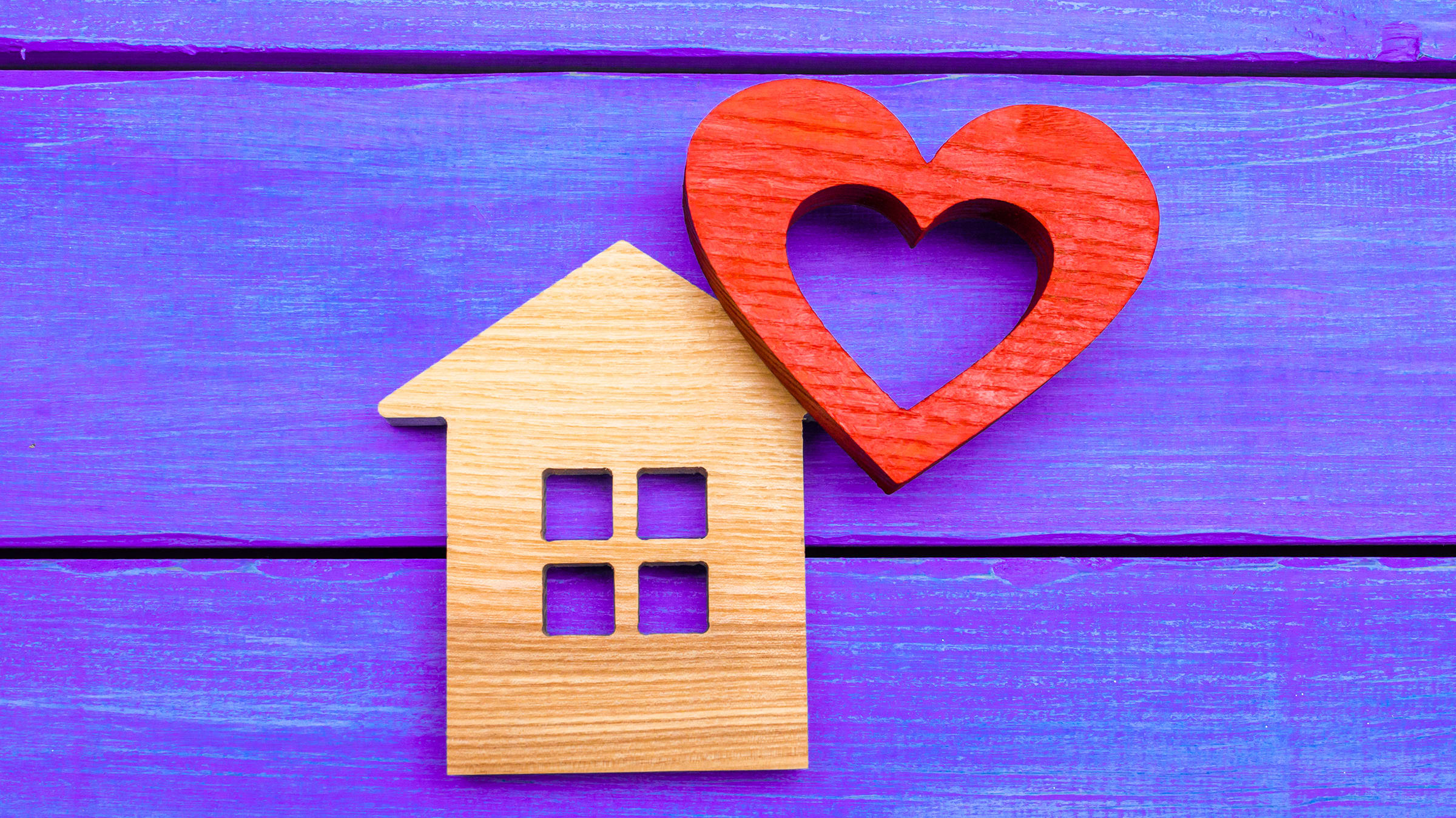 Wooden home cut-out with cut-out wooden heart, symbolizing Yale's home-based care programs