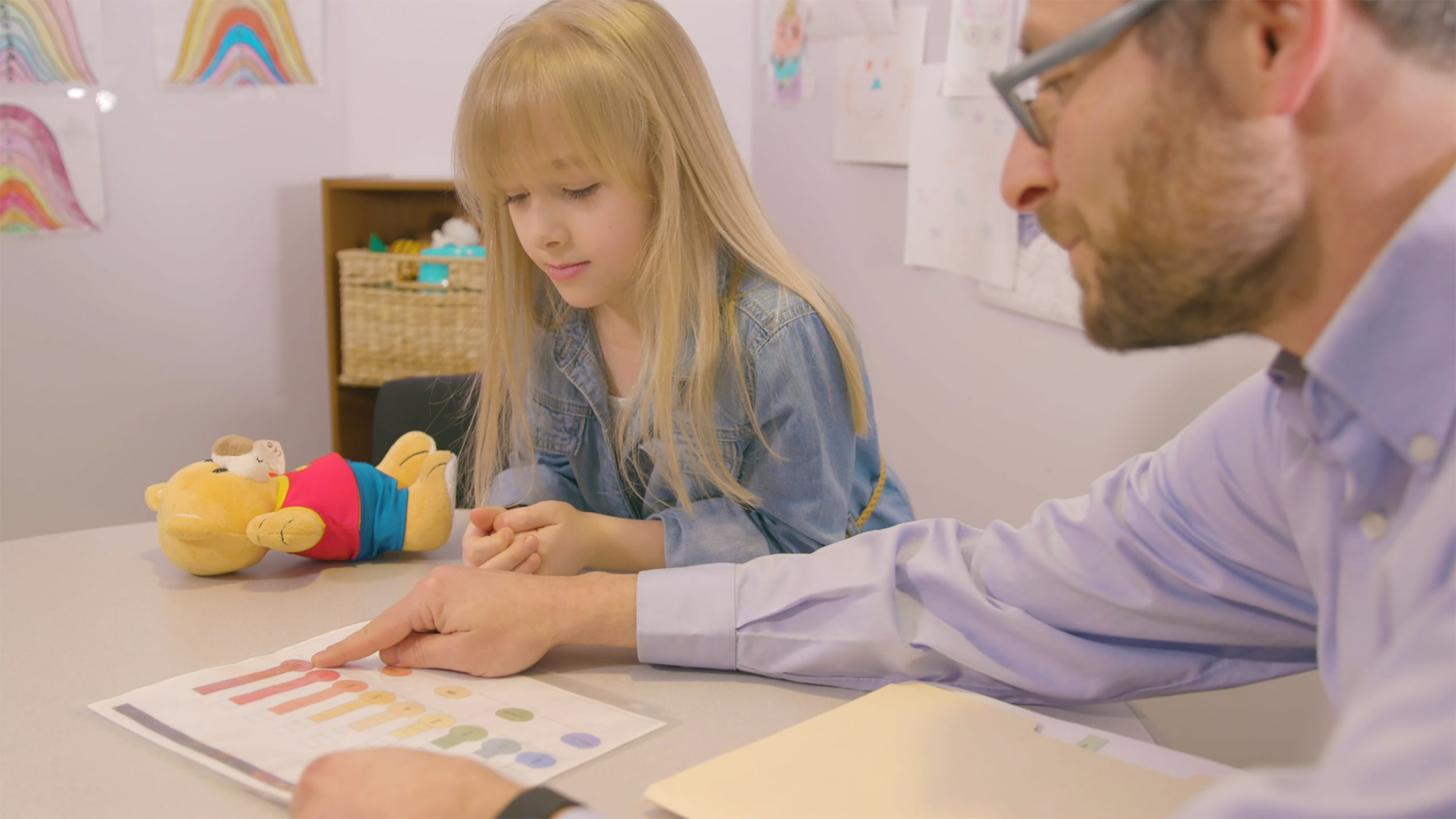 A doctor interacts with a child in a clinic setting.