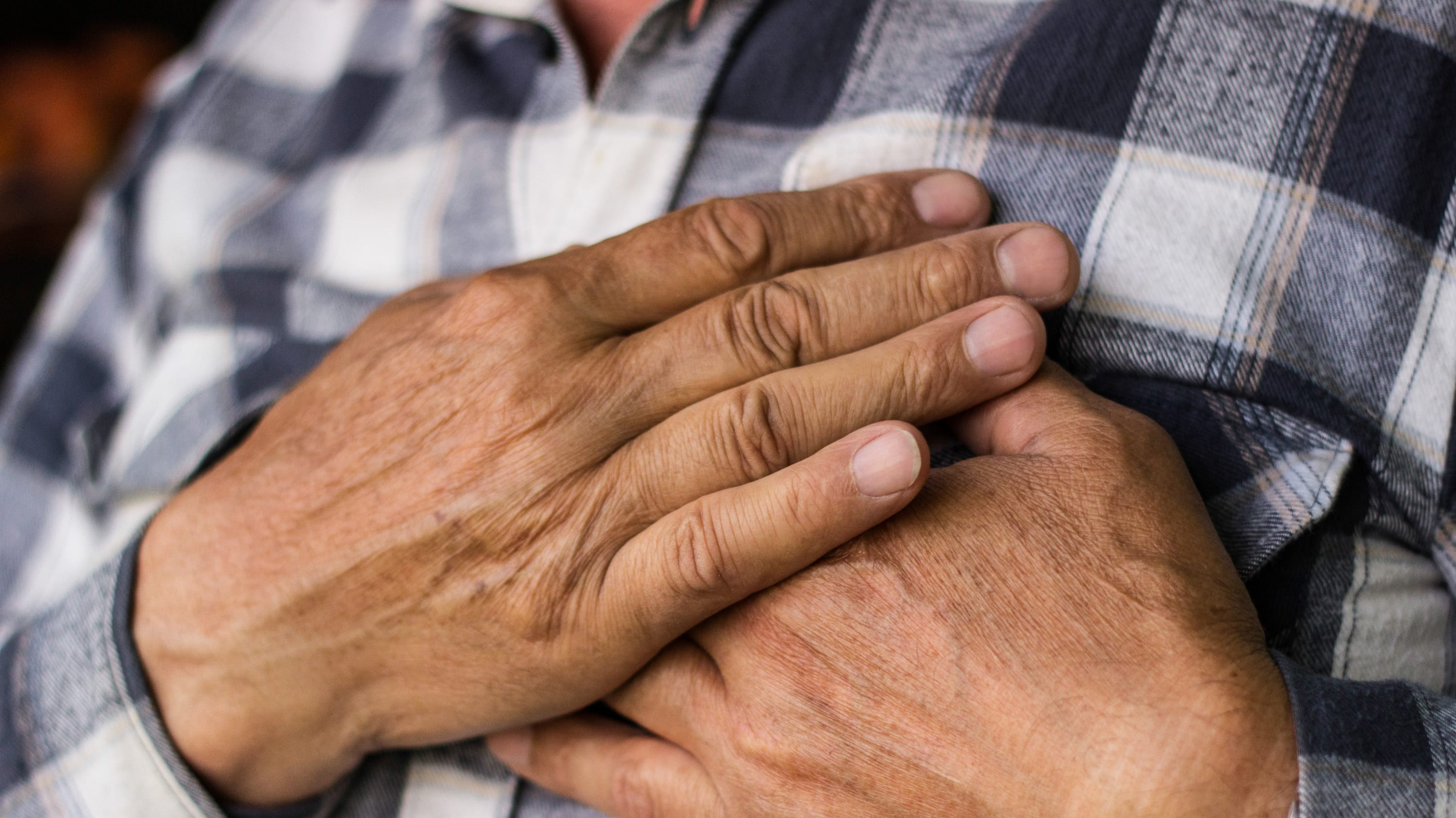 An elderly man clutches his chest in response to pain that could be a sign of a heart attack.
