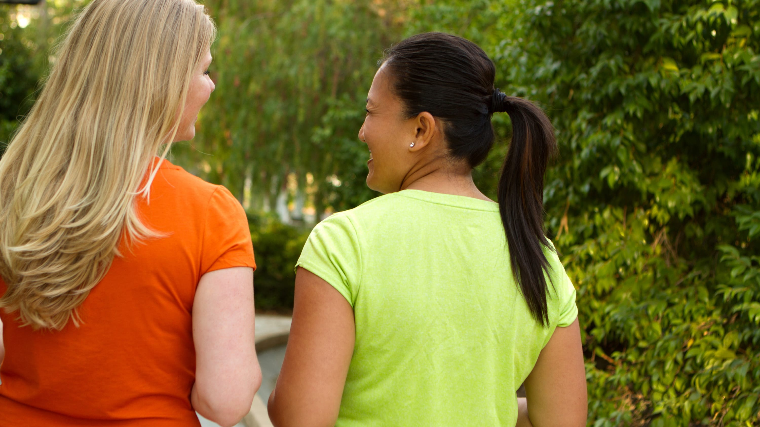 Two women are walking together, knowing that healthy habits can help them avoid heart disease.