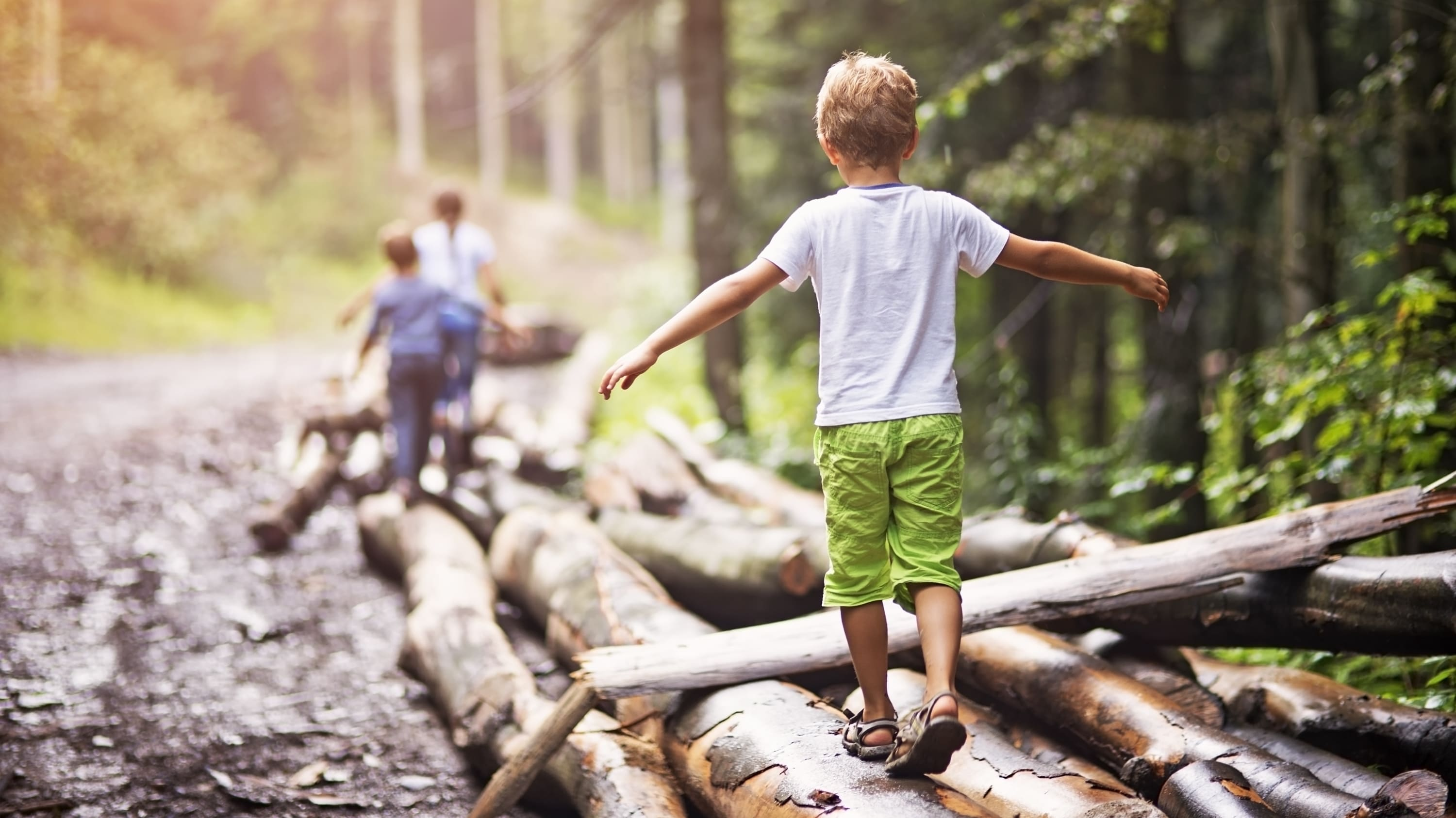 Children who might have juvenile idiopathic arthritis try to balance as they walk across some logs in the woods.