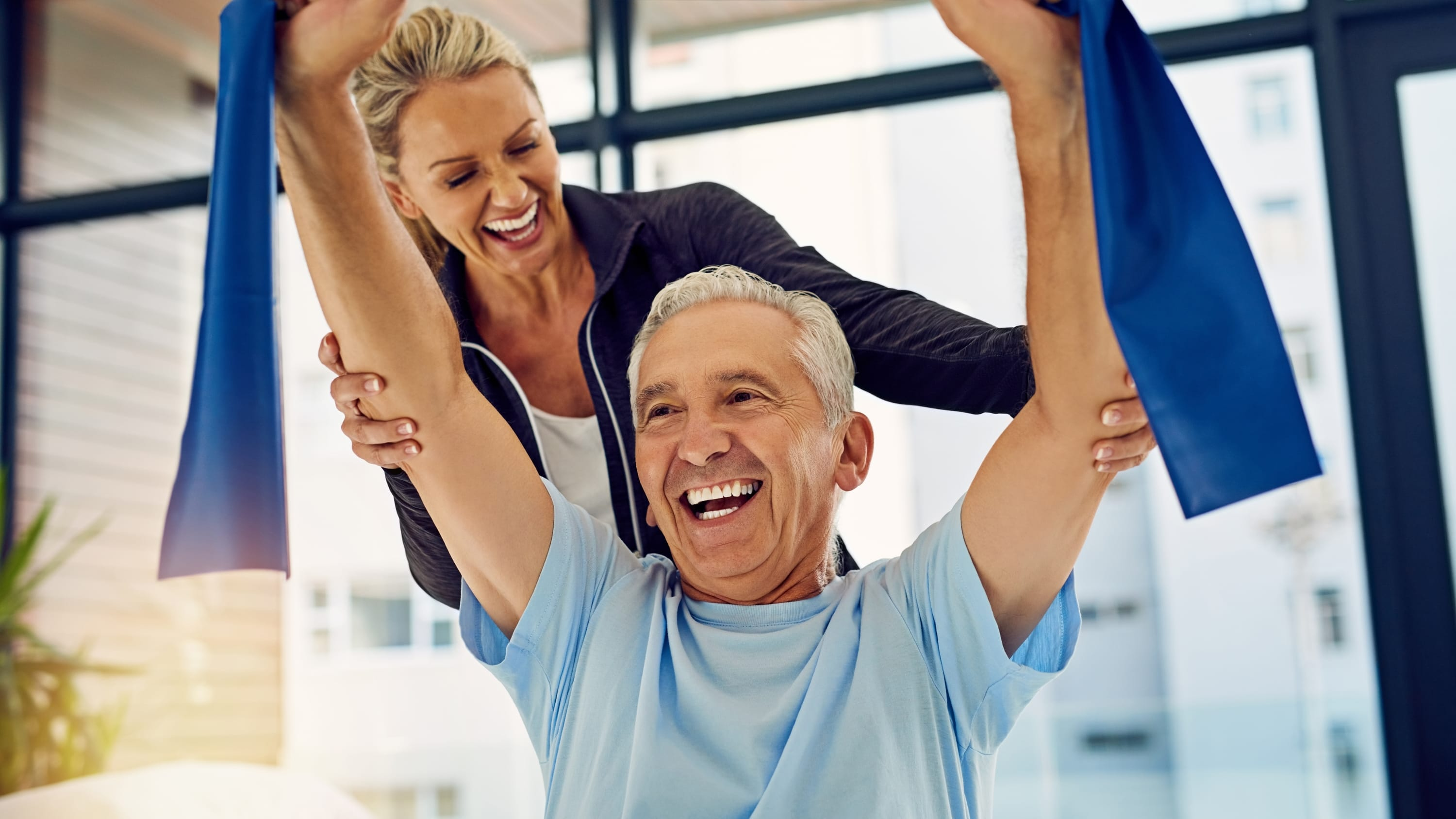 Photograph of a physical therapist helping a senior patient stretch with a stretch band in her office, possibly as part of cancer rehabilitation