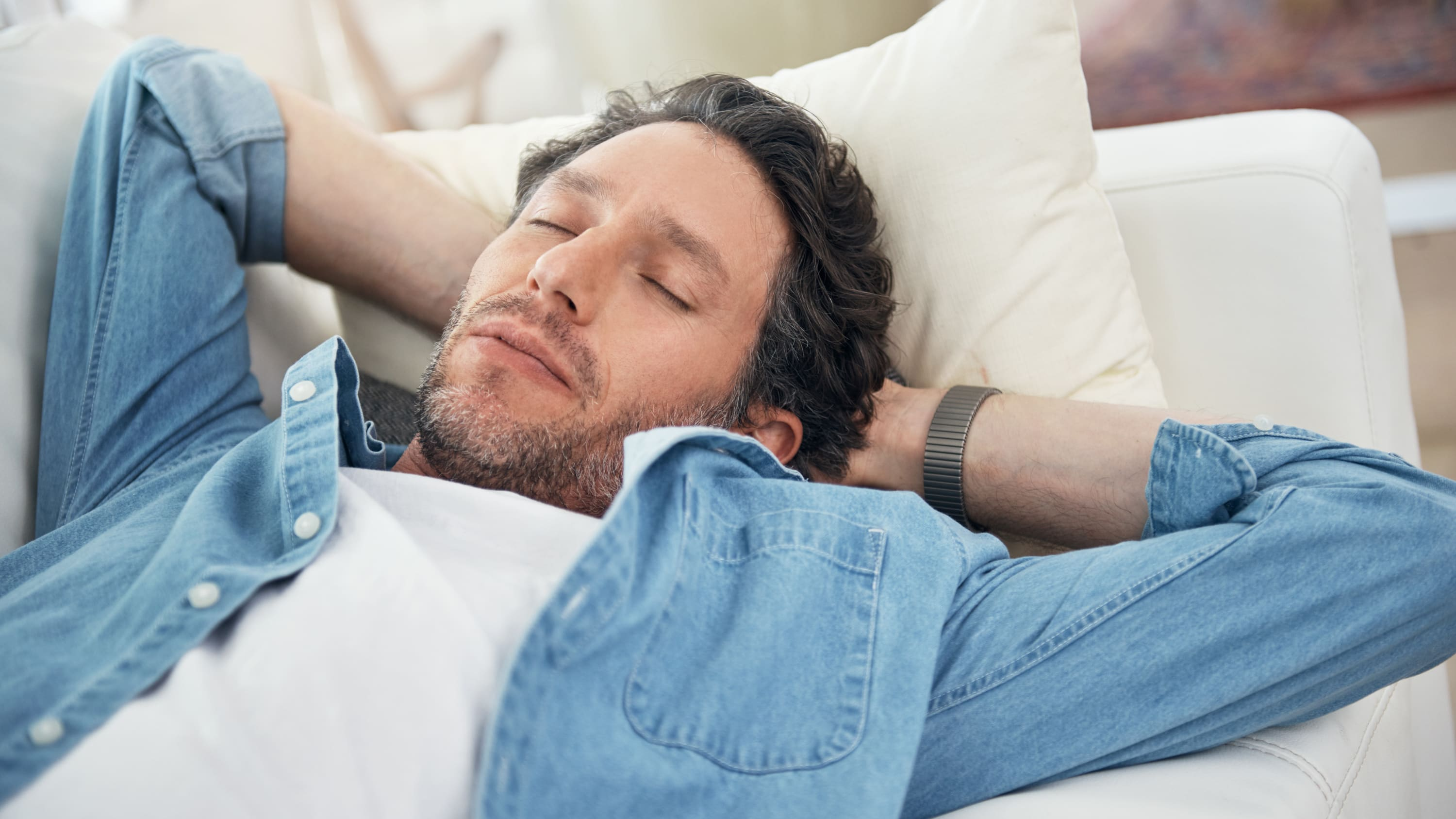 A man relaxes on a bed, possibly someone with marijuana use disorder