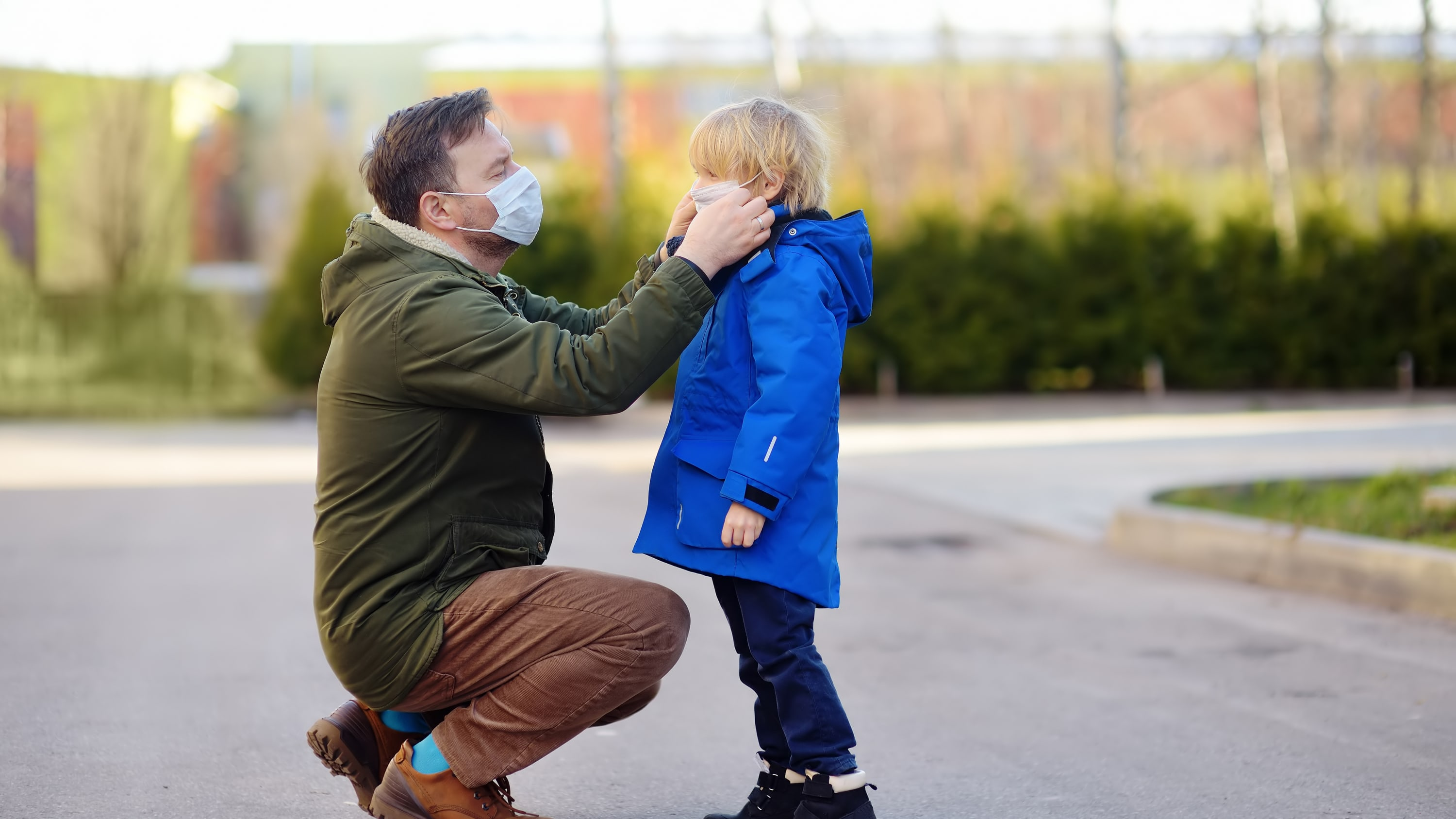 father putting face mask on son, possibly to protect against MIS-C, the syndrome in children associated with COVID-19