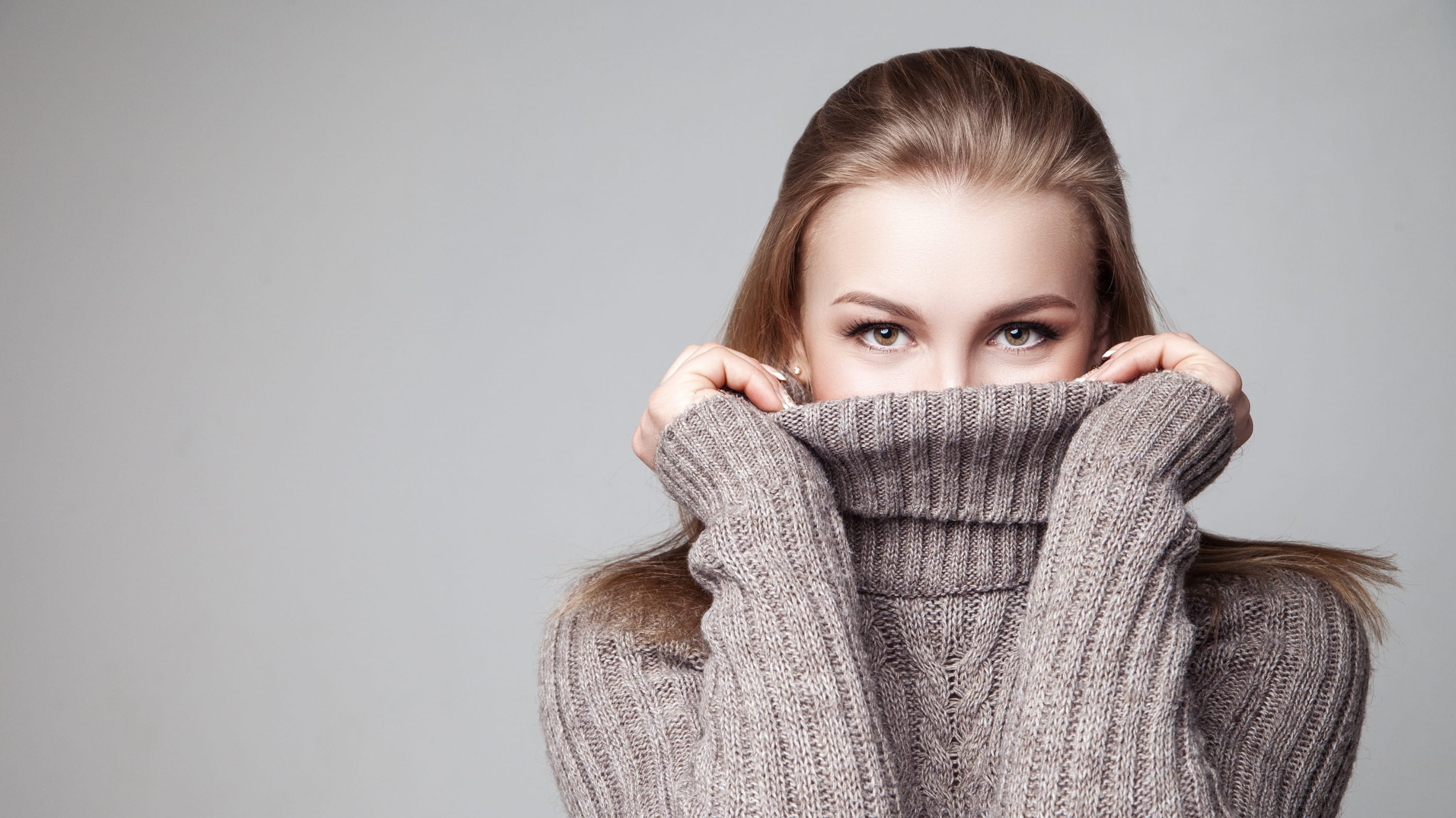 A woman with psoriasis pulling her turtle neck sweater up past her chin.