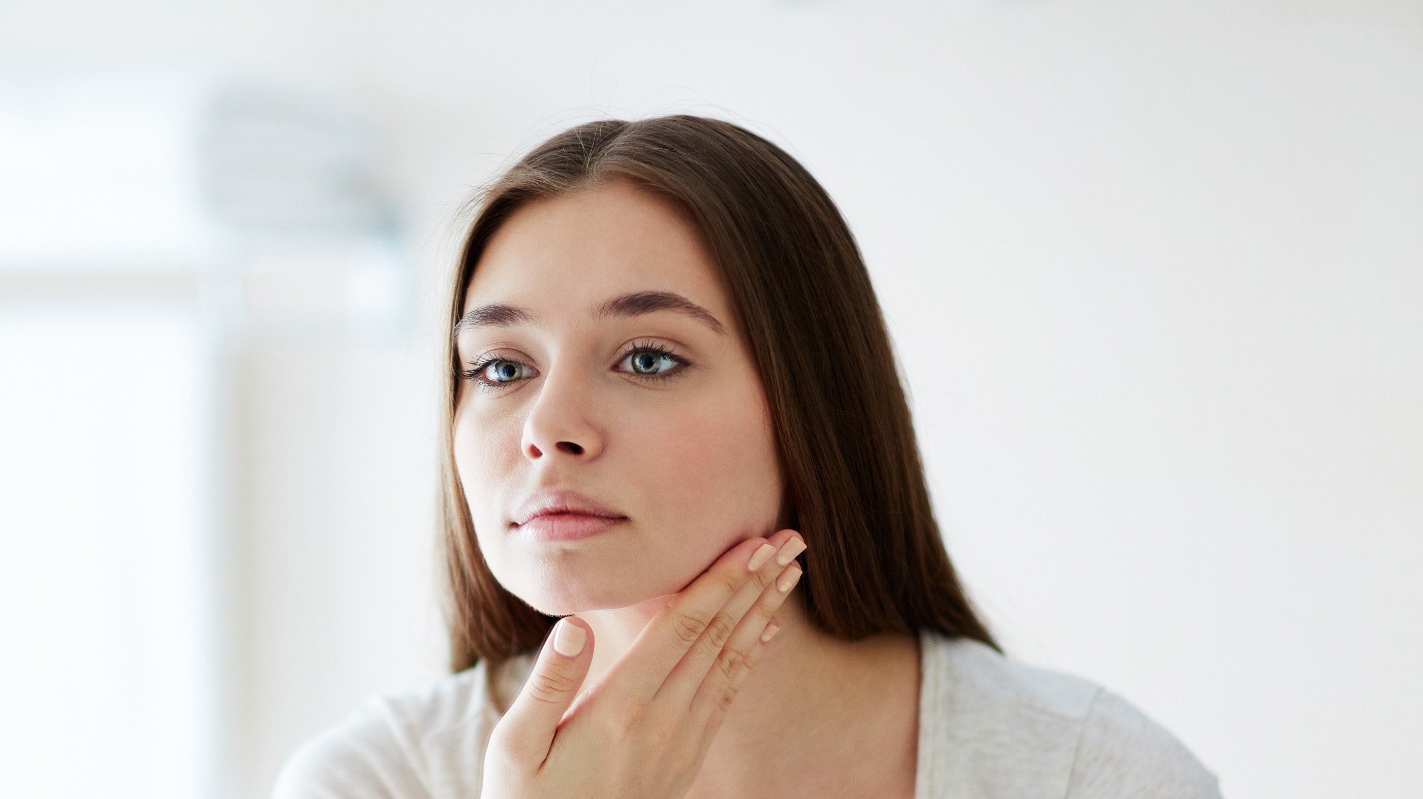 woman looking into a mirror, possibly considering at-home beauty products