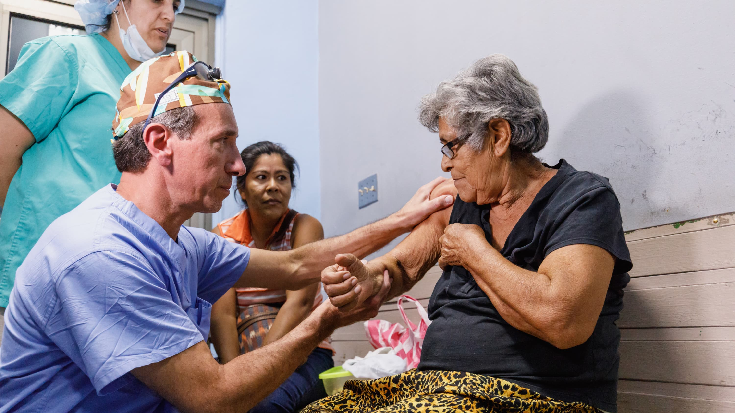 A doctor gently examines an elderly woman's arm and shoulder