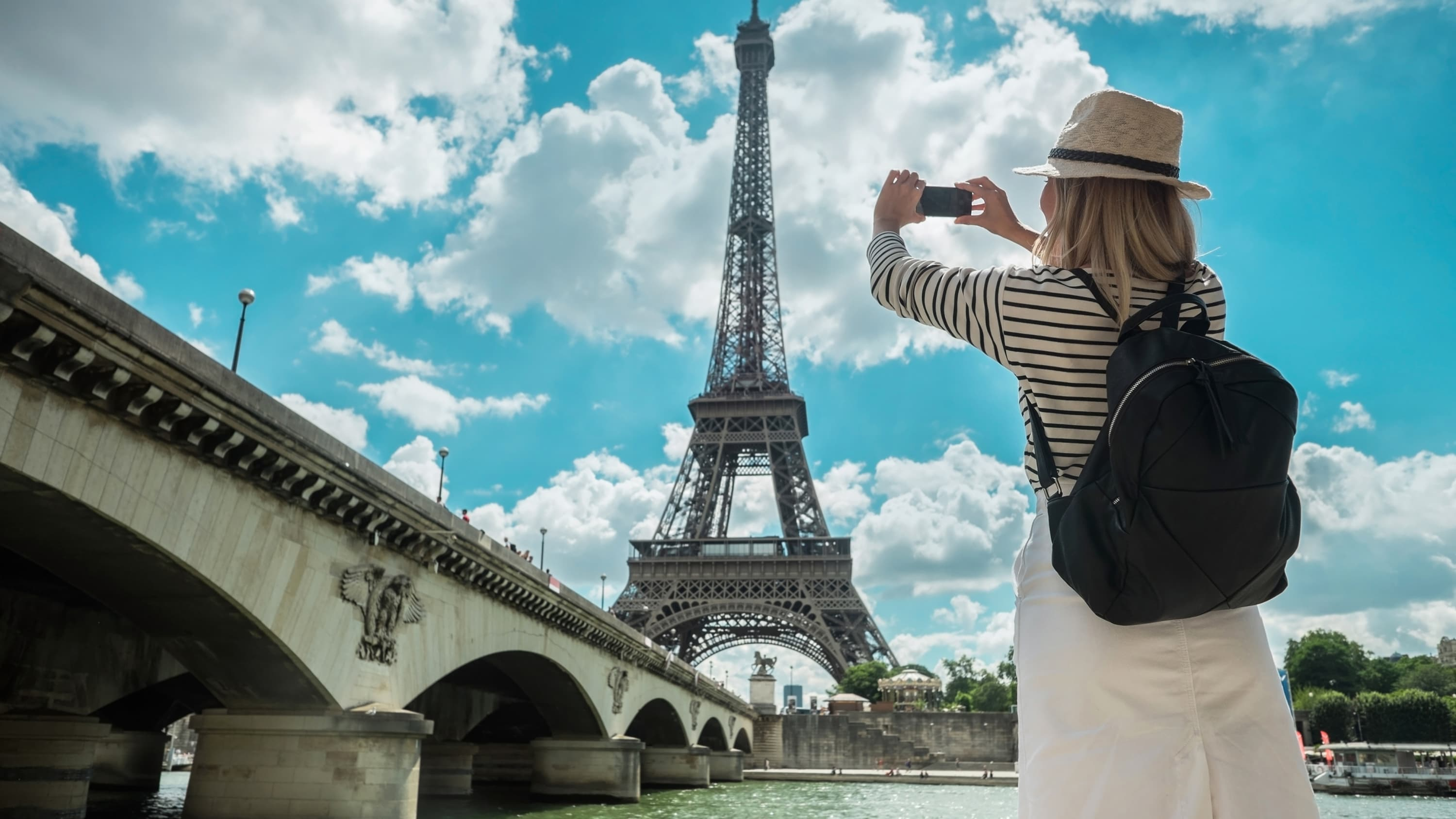 A woman tourist in Paris taking pictures of The Eiffel Tower.