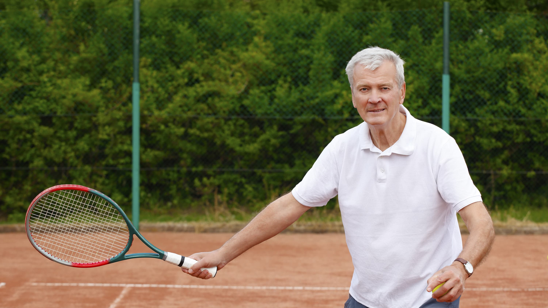 A senior man is playing tennis.