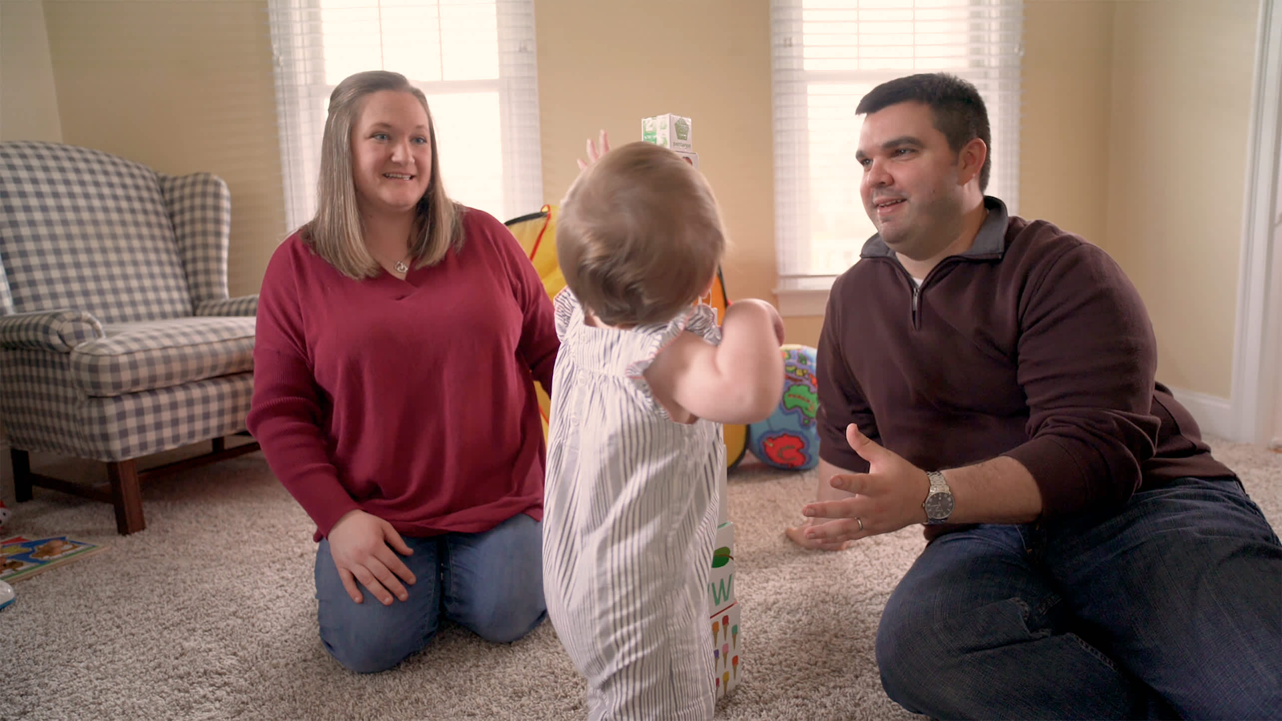 A mother and father play with their baby daughter.