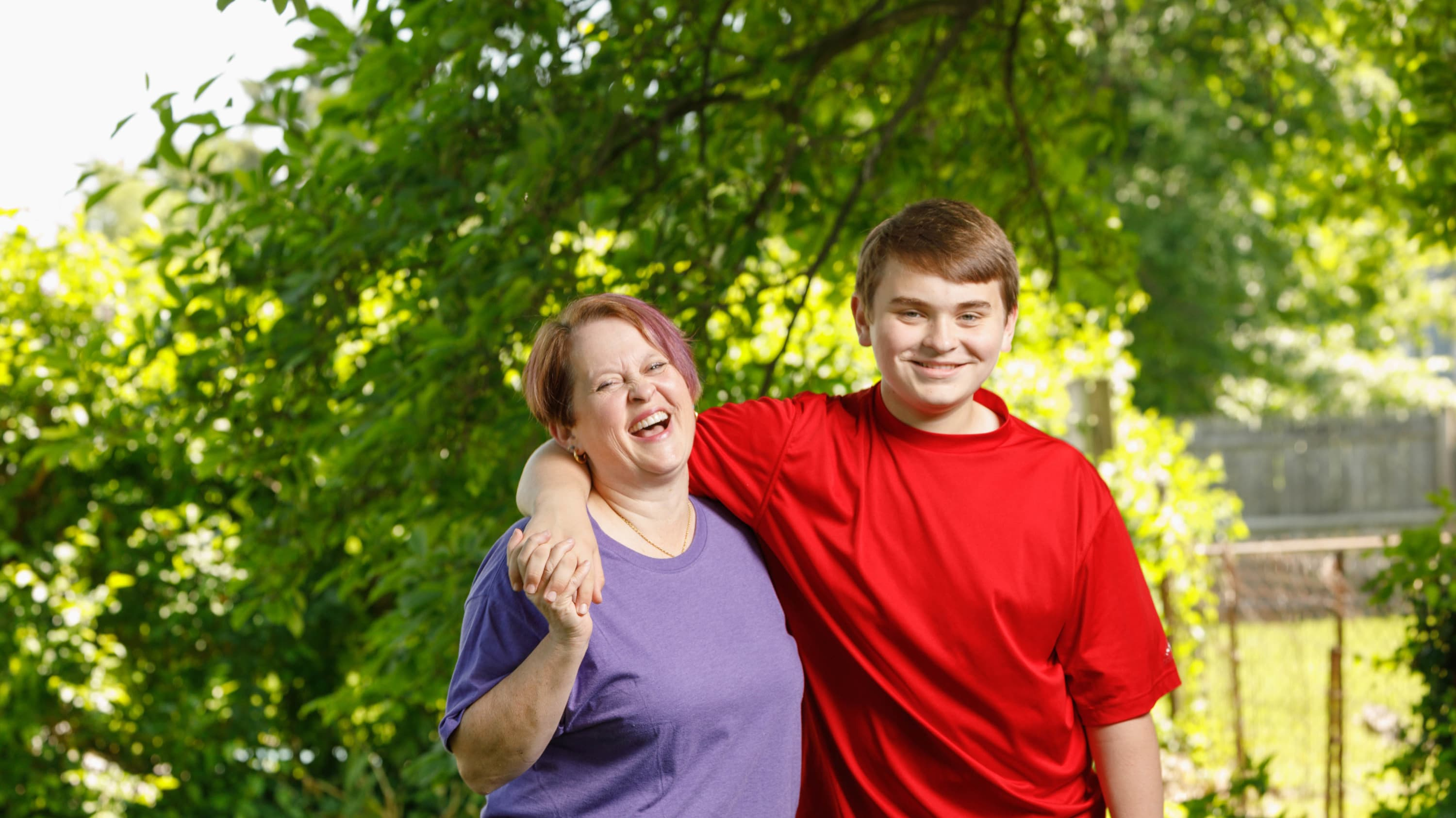 A mother and son stand in their backyard smiling and laughing.