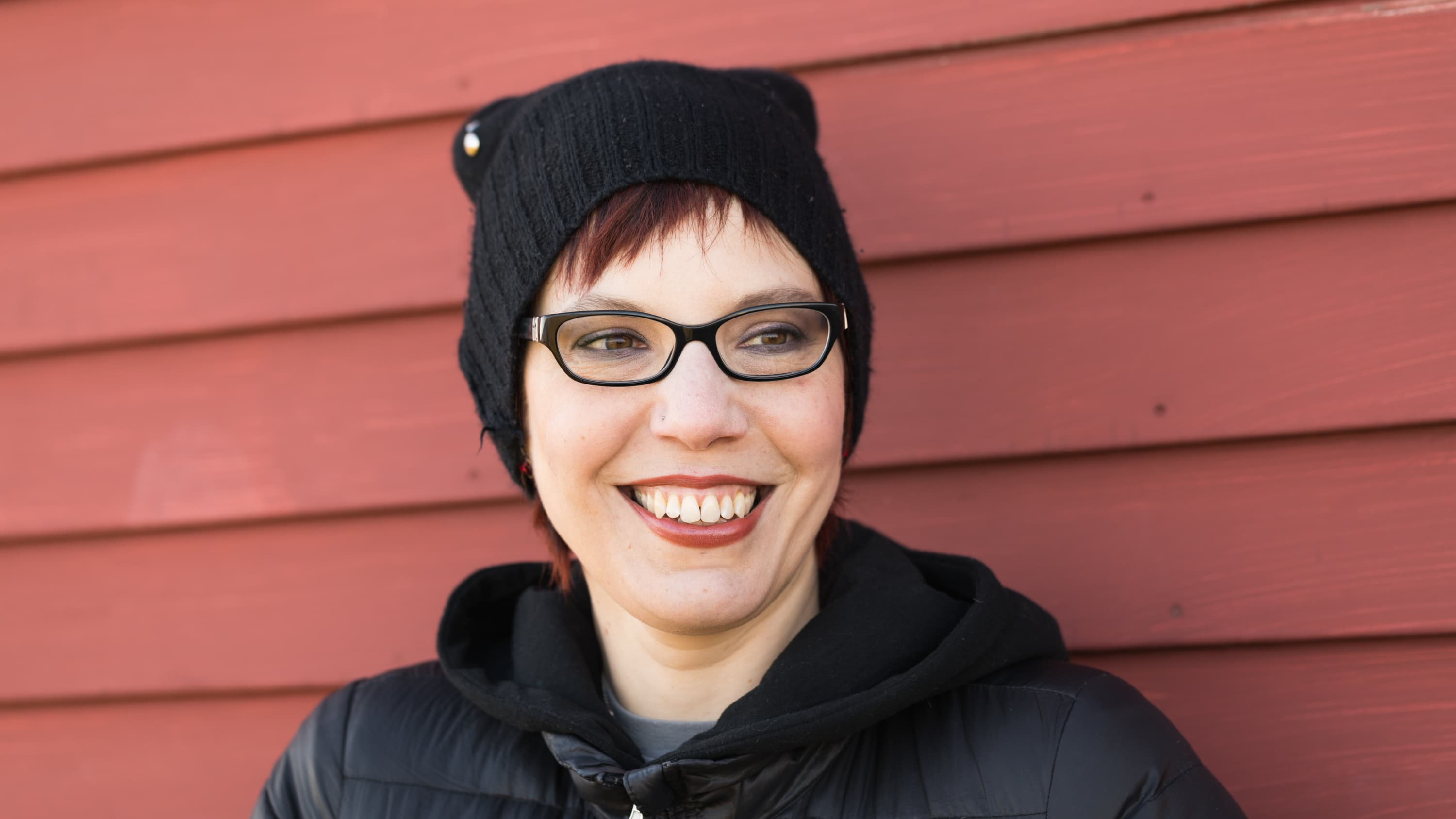 Erika Lewis, with glasses and knit hat, smiles into the camera.