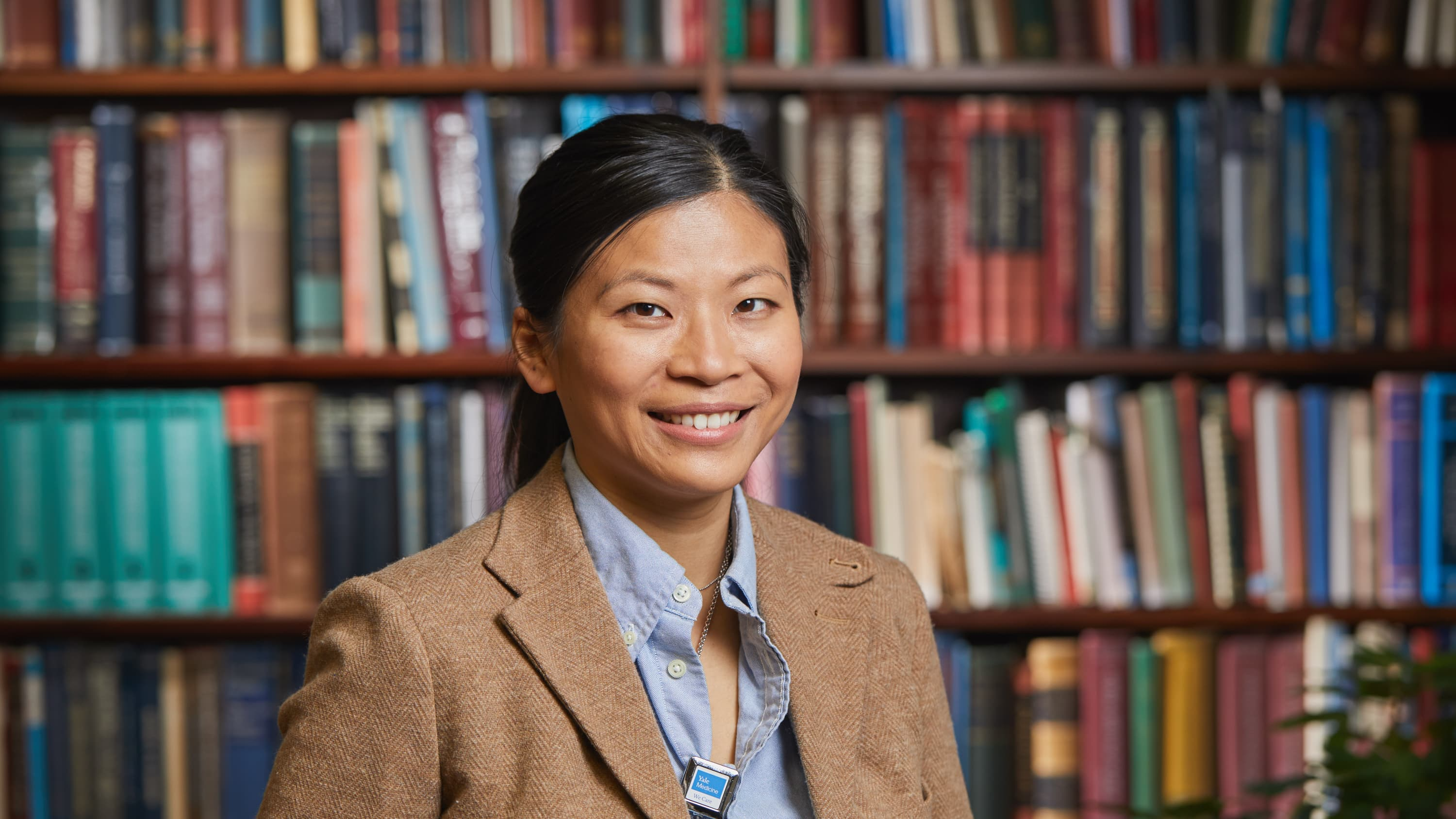 Dr. Yan Ho Lee stands in front of a bookcase in the otolaryngology office.