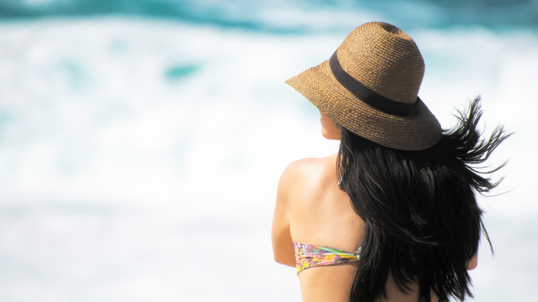 Woman on beach with long dark hair wearing hat.