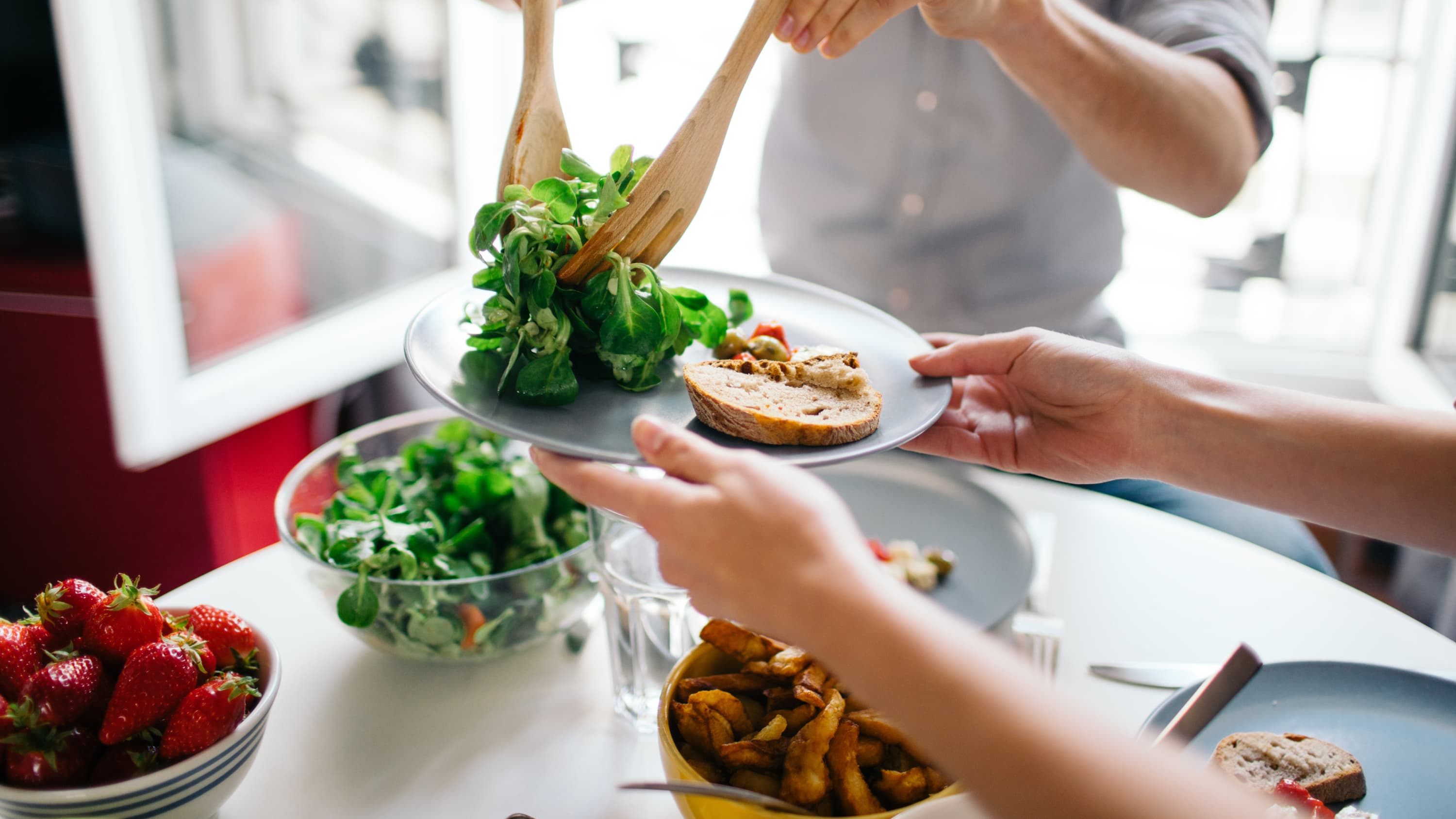 At a dinner table, one person extends their plate as another person serves salad.