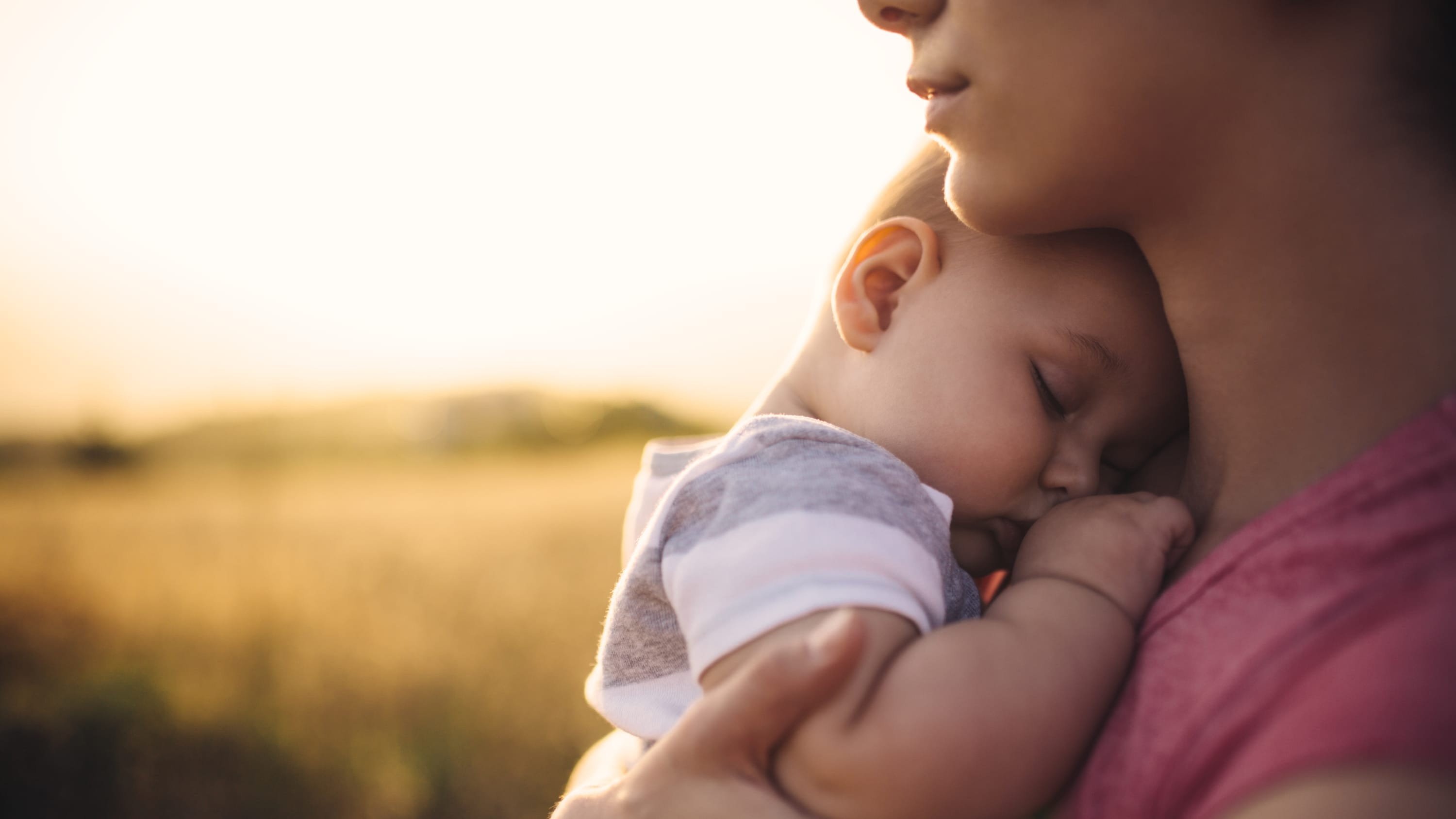 A woman holds her napping son.