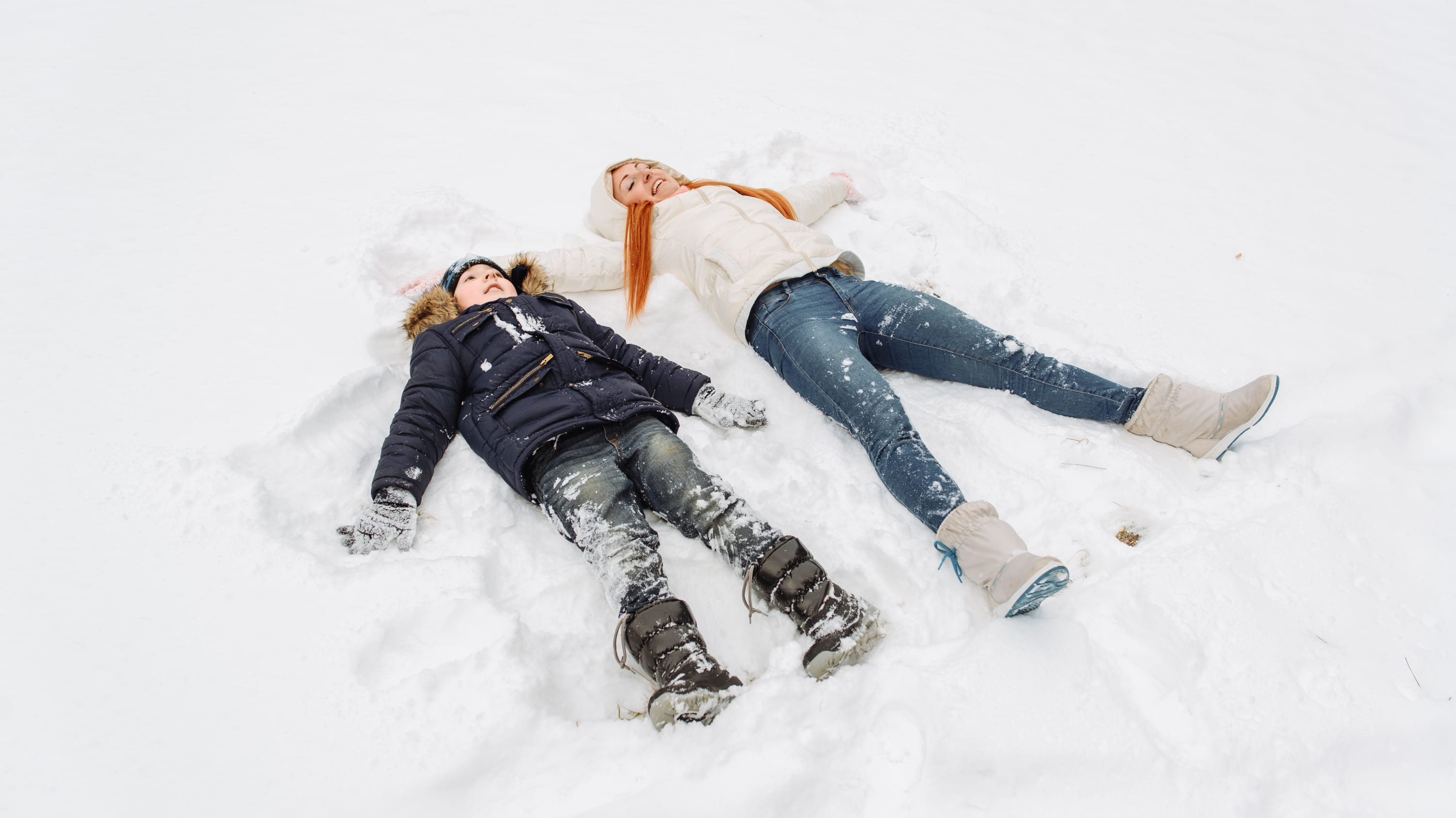 A brother and sister in their winter coats, boots and hats are making angels in the snow.