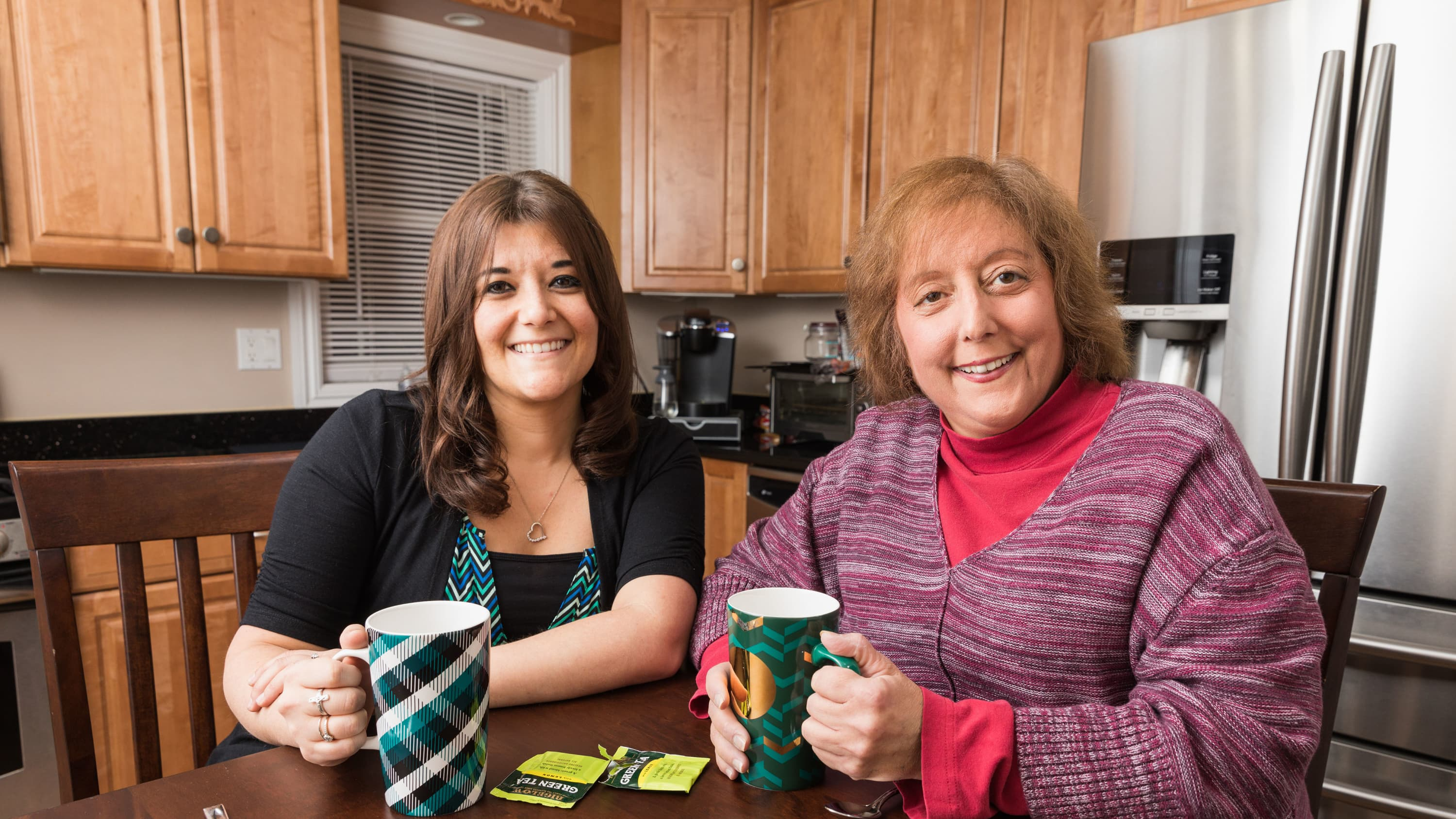 Annamarie Williams (left) and her mom, Sally Proto, pose together in a kitchen.
