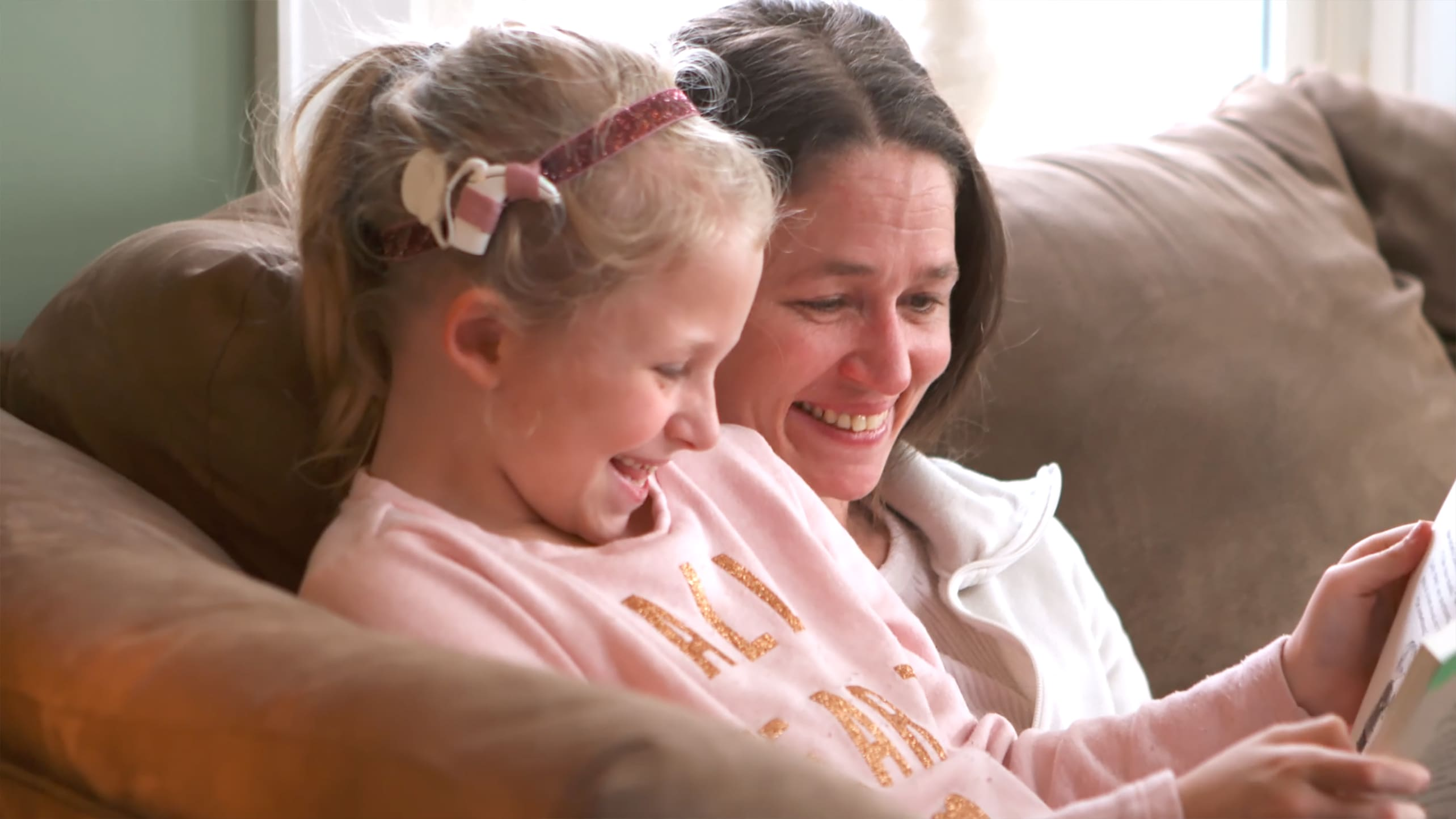 A little girl with a cochlear implant reads with her mother.
